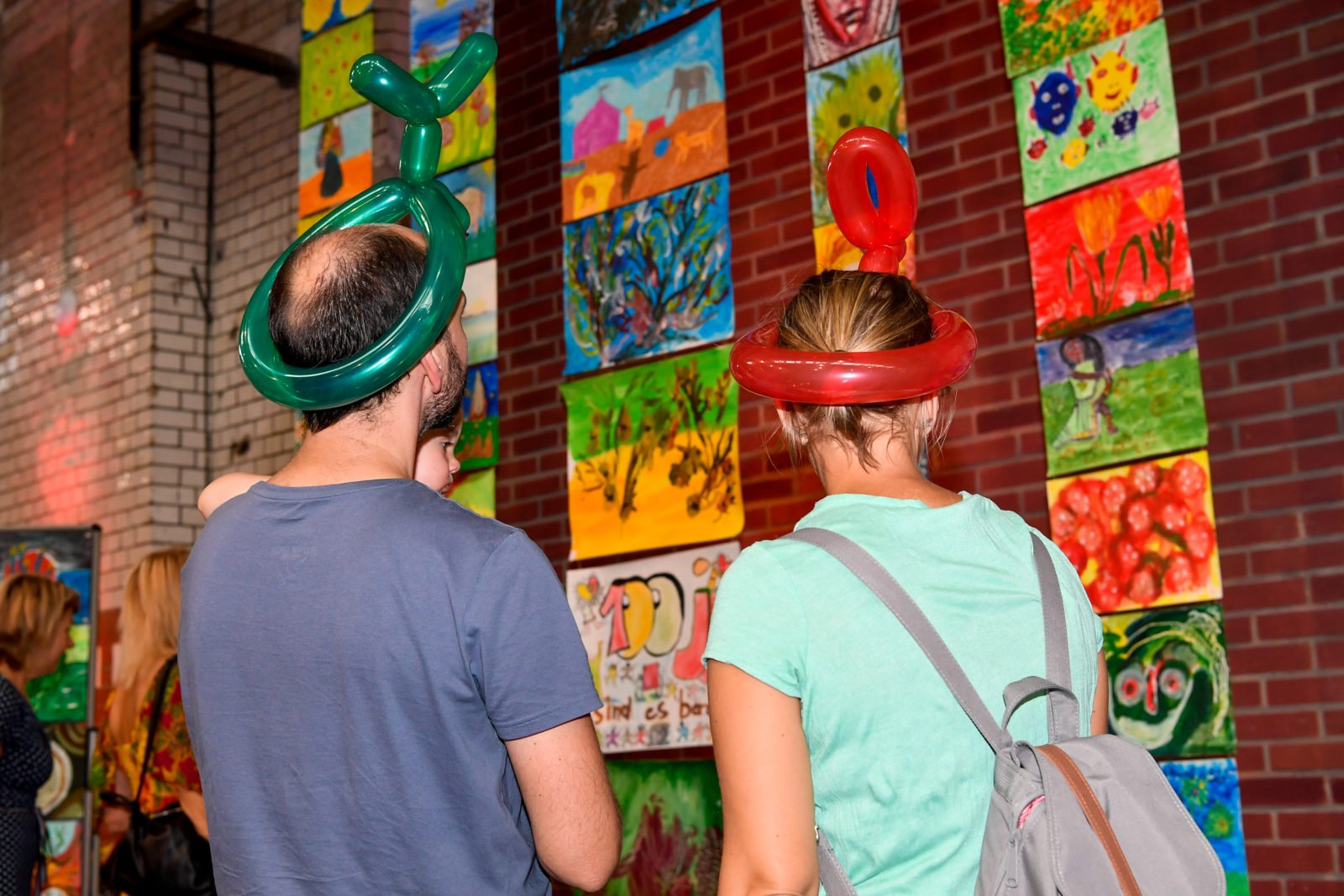 Zwei Menschen stehen vor der Bilderwand der Kunstgruppen auf dem Fest zum 100-jährigen Jubiläum der Stiftung