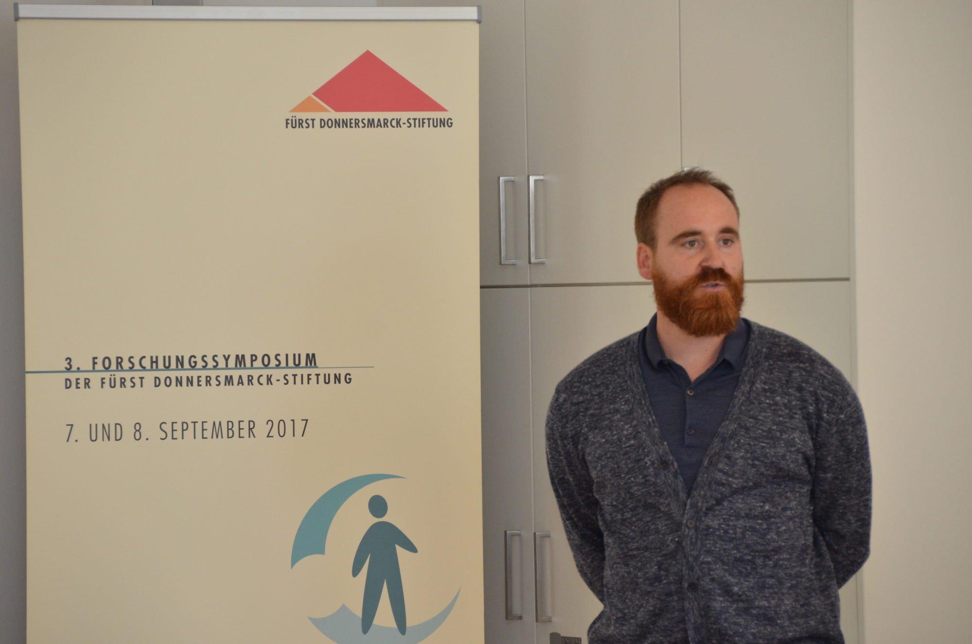 """Christian Schlenstedt steht vor einem Banner """"3. Forschungssymposium der Fürst Donnersmarck-Stiftung 7. und 8. September 2017"""". Er trägt einen grauen Strickpullover und hat die Arme hinter dem Rücken verschränkt."""