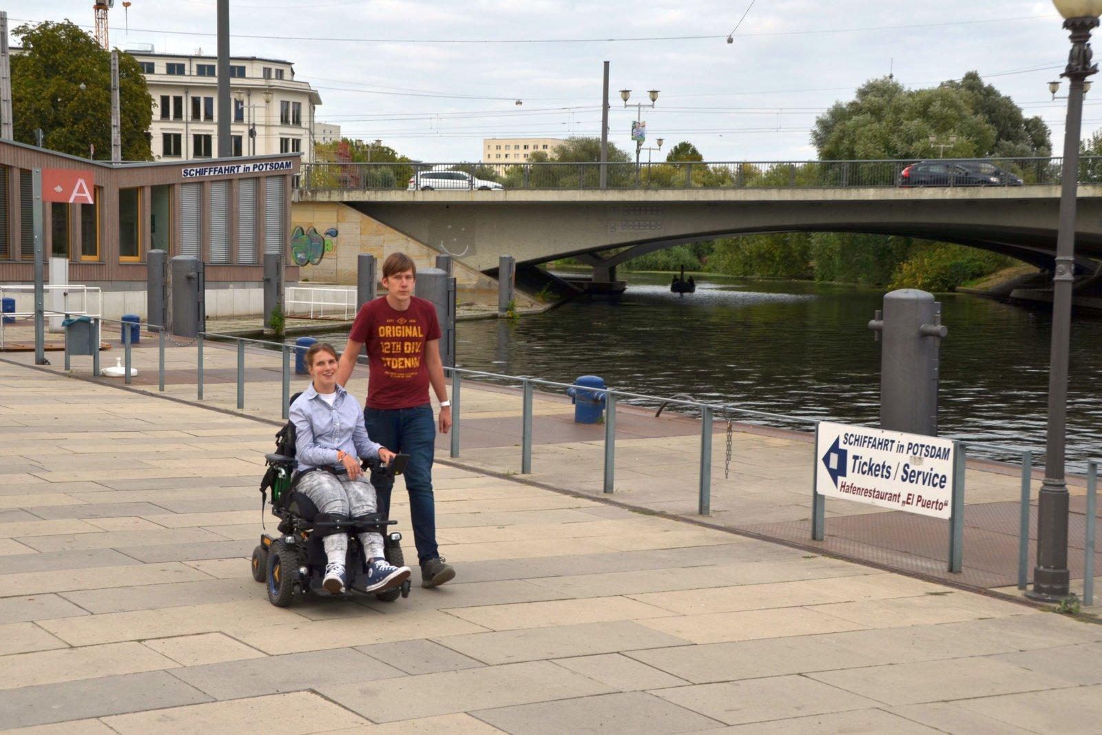 Lea Voitel und ihr Freund beim SPaziergang am Potsdamer Hafen. Sie sitzt im E-Rollstuhl, er leäuft rechts neben ihr.