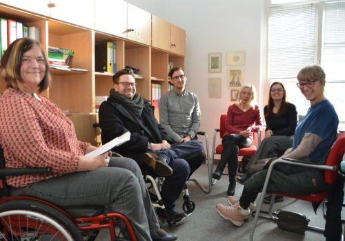 Eine Gruppe Menschen sitzt im Gesprächskreis. Links eine junge Frau und ein junger Mann im Rollstuhl.