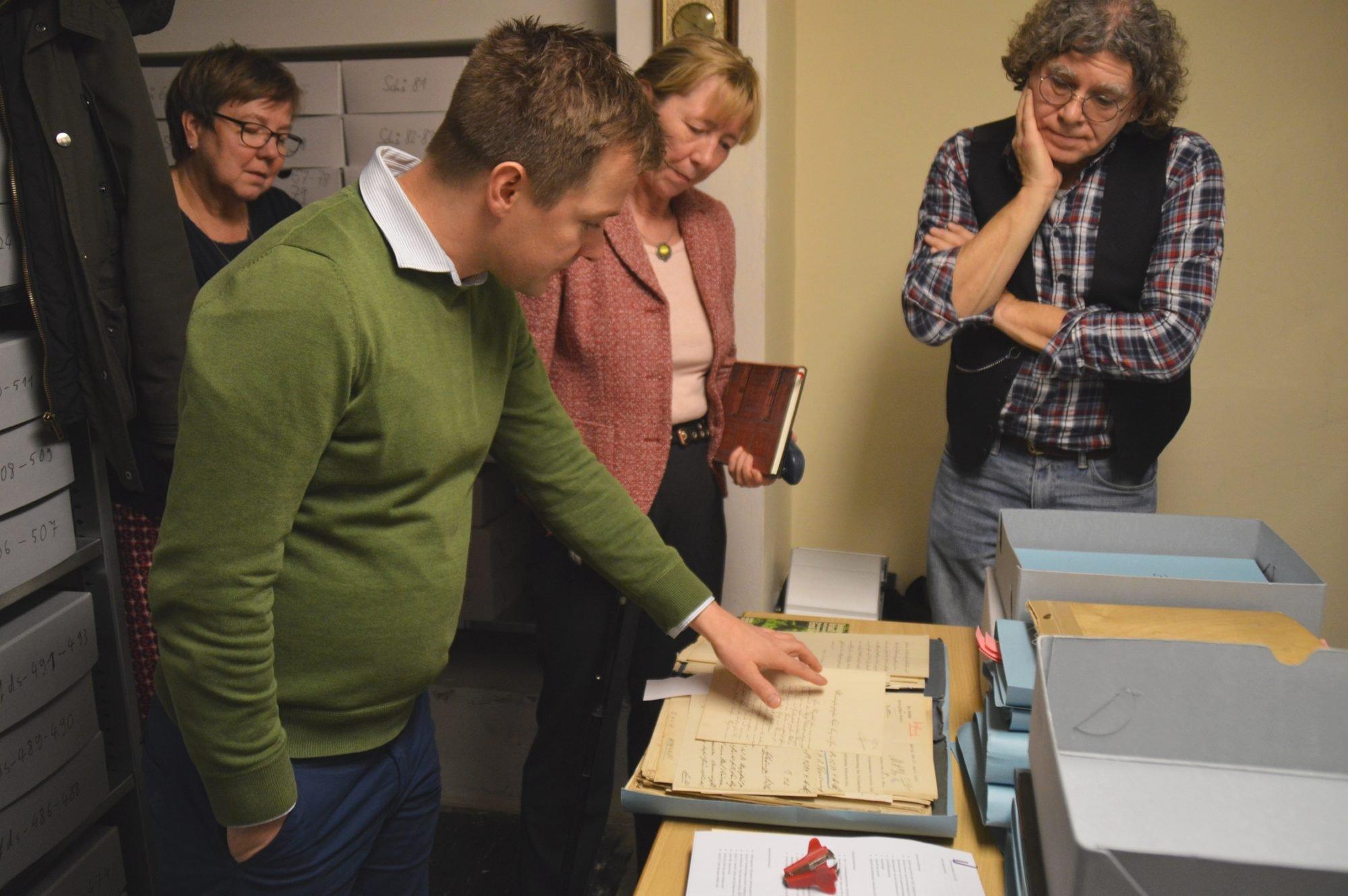 Vier Personen stehen im alten Archivraum um einen Tisch herum und betrachten alte Akten.