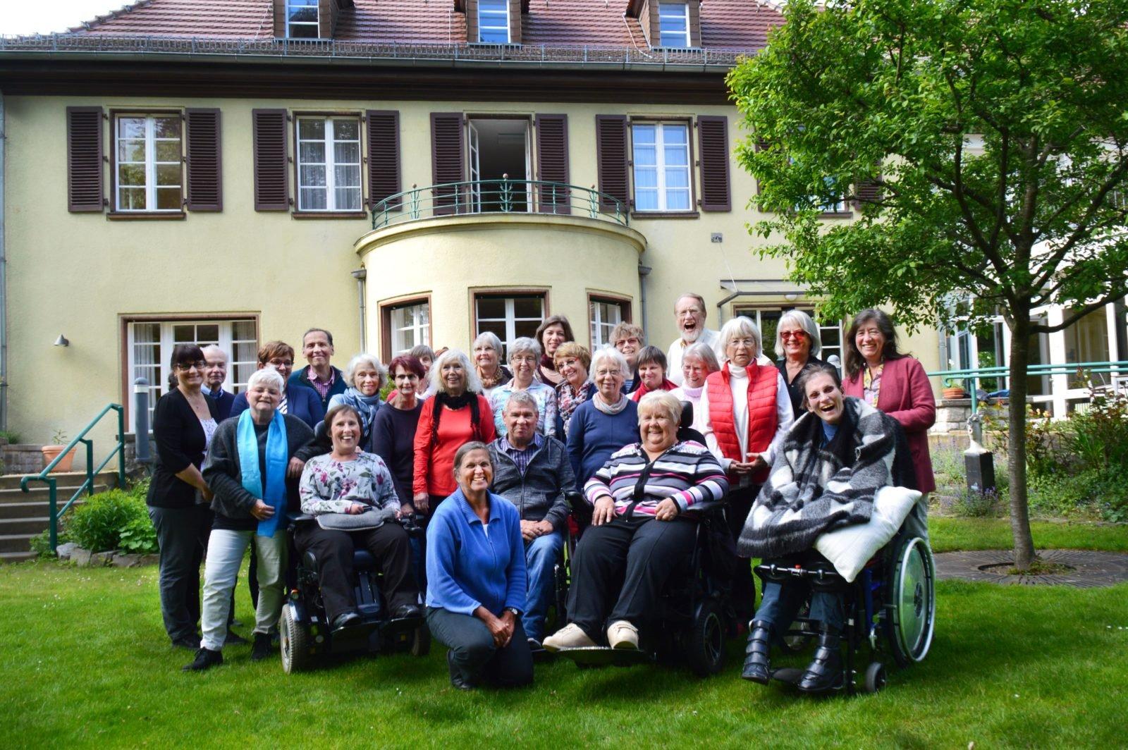 Eine Gruppe posiert vor einer Villa