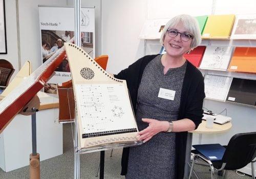 Eine Frau hält eine kleine Harfe in dem Arm und lächelt in die Kamera