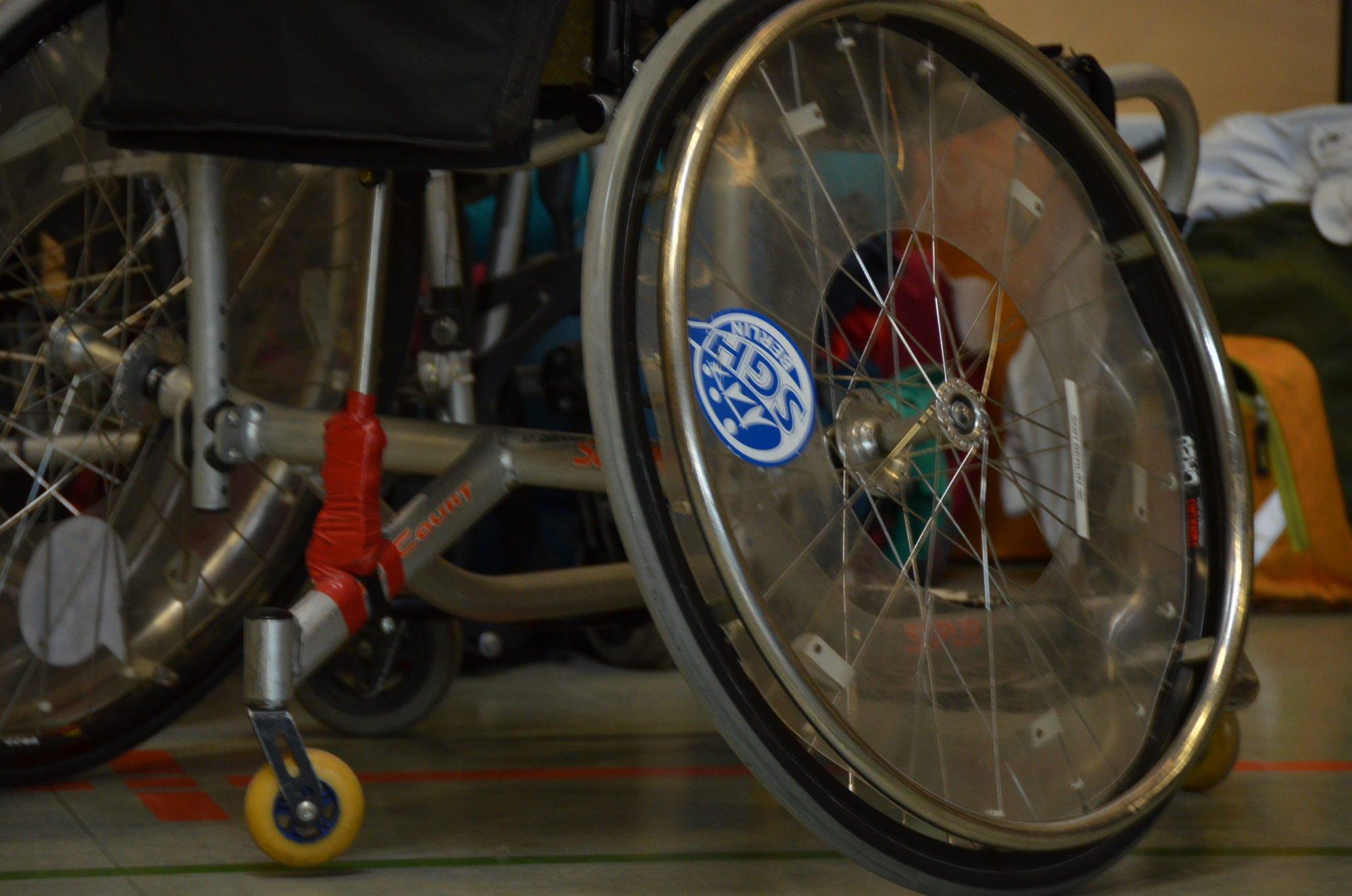 Nahaufnahme eines Rollstuhl-Rades mit SGH Aufkleber.