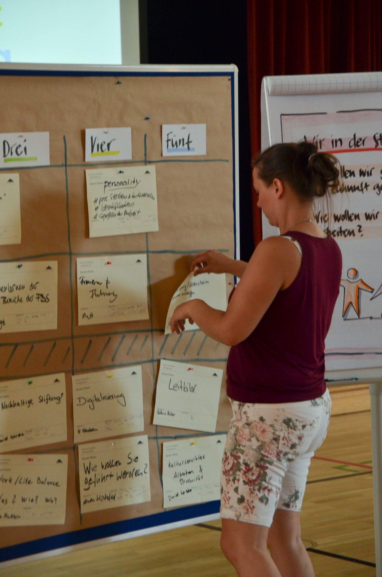 Yvonne Grabow pinnt eine Moderationskarte an eine braune Metaplanwand.