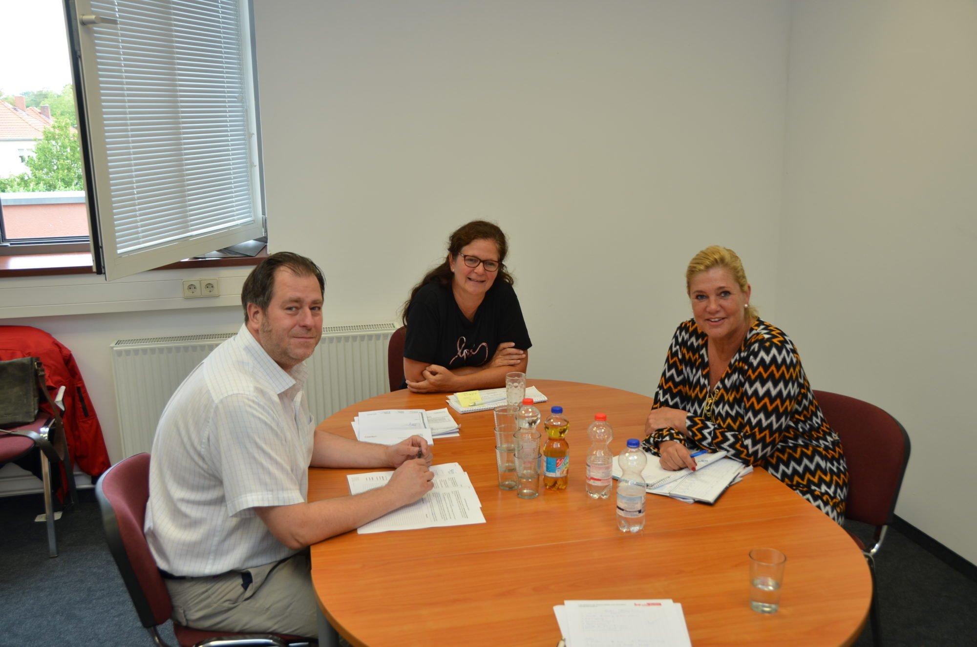 Die Pflegedienstleitung sitzt an einem Tisch. Von links nach rechts sitzen Andreas Seitz, Kathleen Beyer und Anett Leonhardt