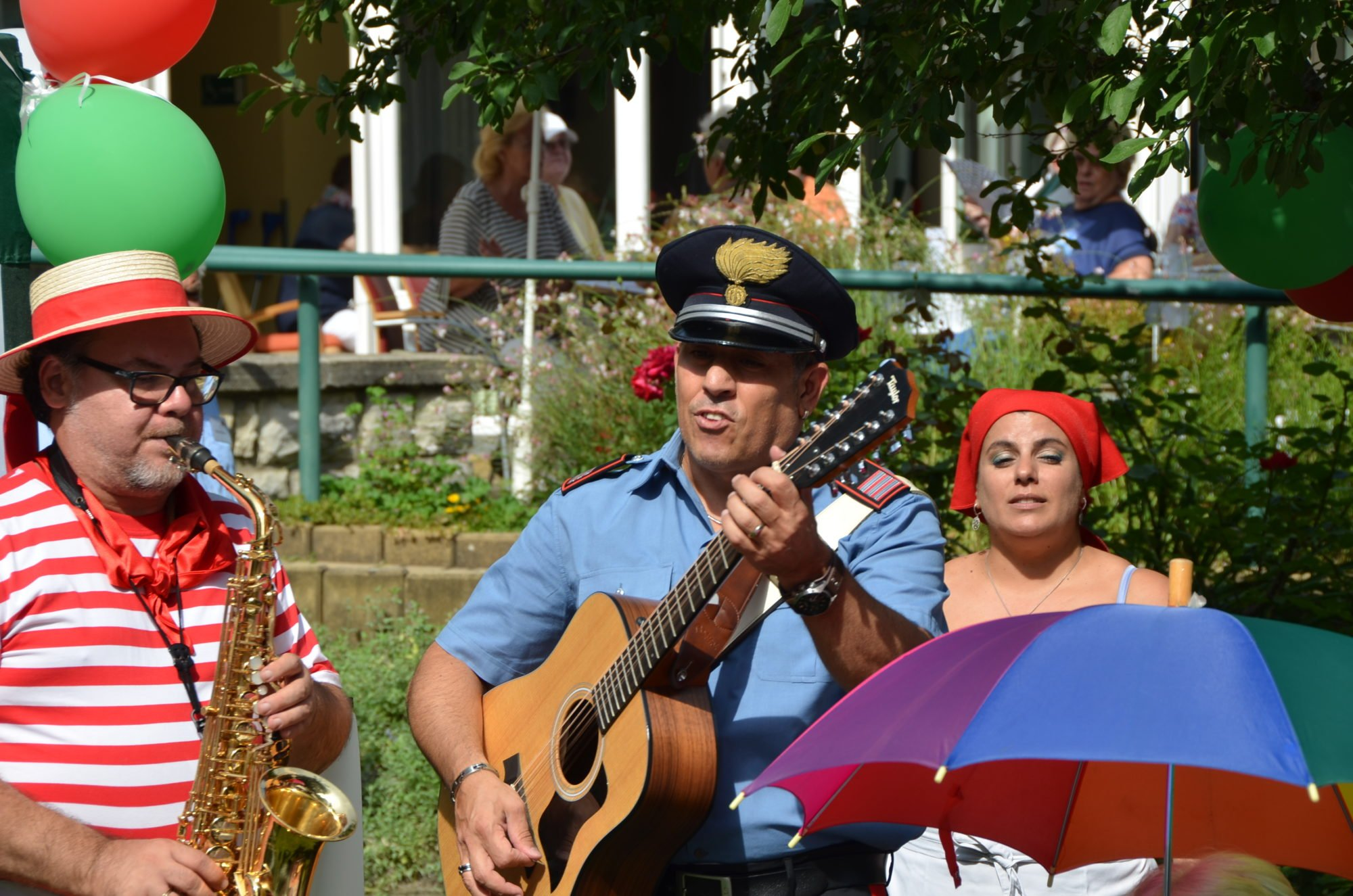 Drei Musiker - zwei Männer und eine Frau - spielen auf dem italiensichen Sommerfest der Villa Donnersmarck Musik. Ein Mann spielt Saxofon, ein weiterer Gitarre, die Frau singt.