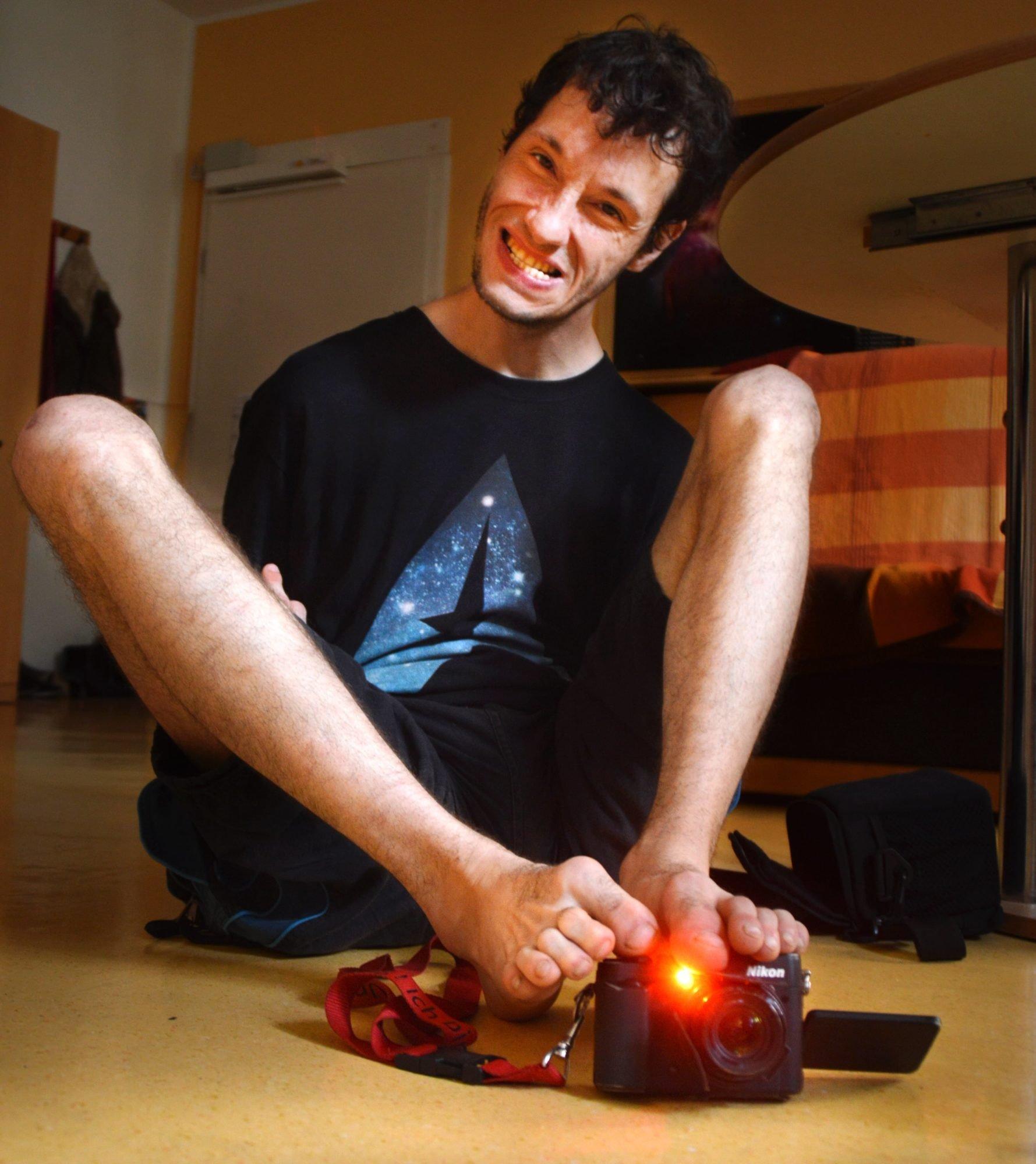 Fotograf Sven Kocar, lachend auf dem Fußboden seiner Wohnung sitzend, in seinen Füßen eine Digitalkamera, deren rotes aufnahmelämpchen leuchtet