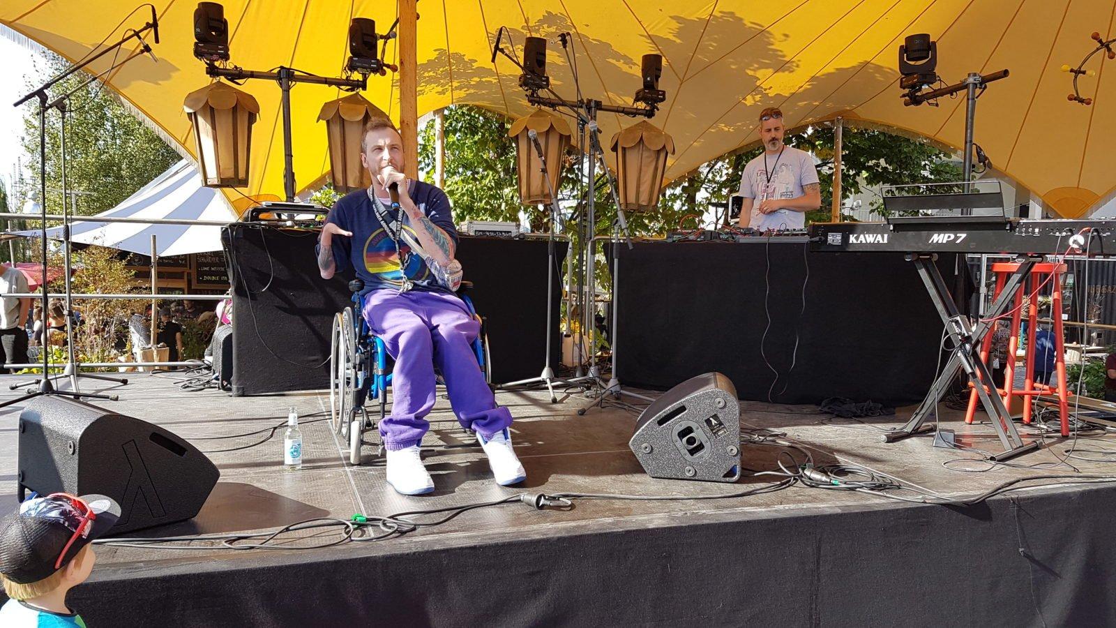 Mann im Rollstuhl singt mit Mikrofon in der Hand auf der Bühne