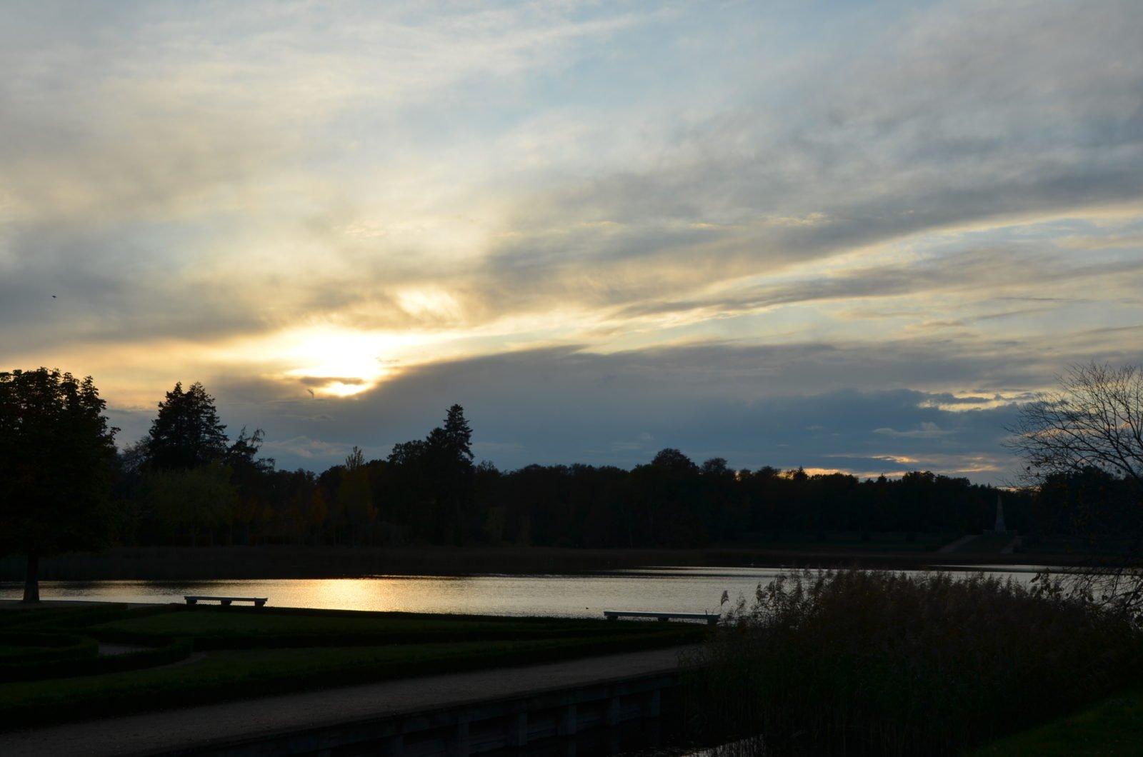 Ein Sonnenuntergang bei wolkenbedecktem Himmel, direkt am Wasser. Über den See hinweg sind im Hintergrund sind ein Wald und ein Obelisk.