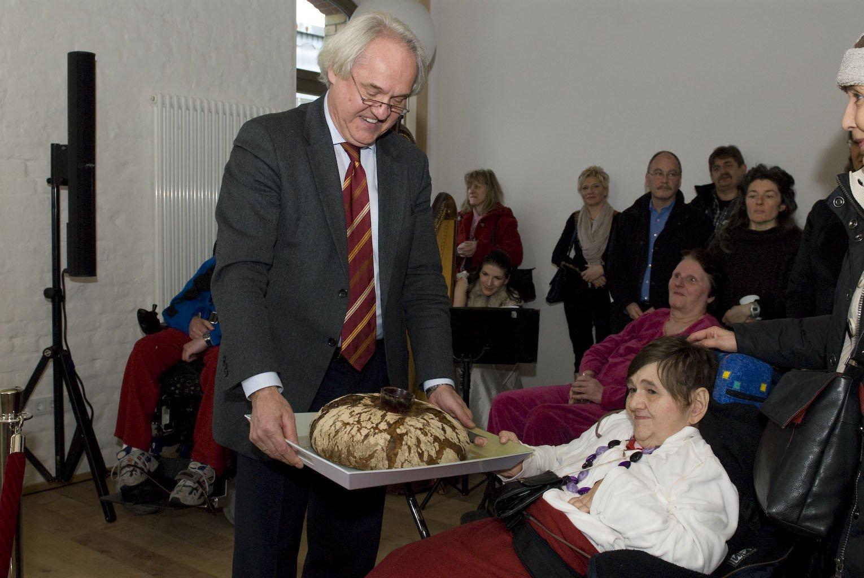Wolfgang Schrödter überreicht einer Bewohnerin des WmI Pankow das symbolische Brot und Salz.