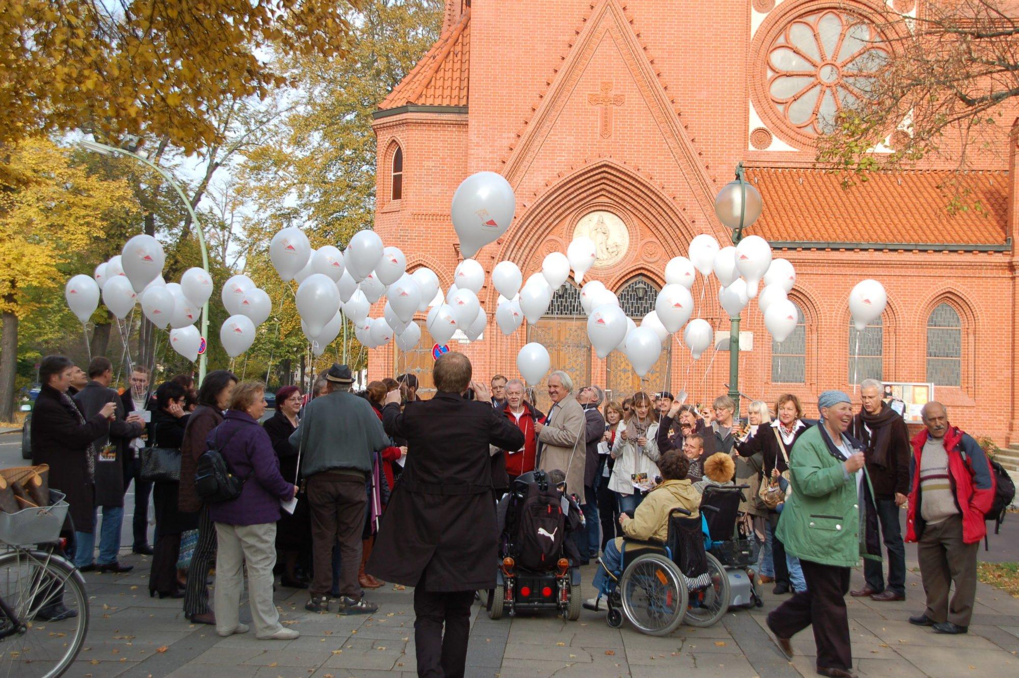 Eine große Menschentraube - zu Fuß und im Rollstuhl. Alle halten weiße Luftballons in den Händen.