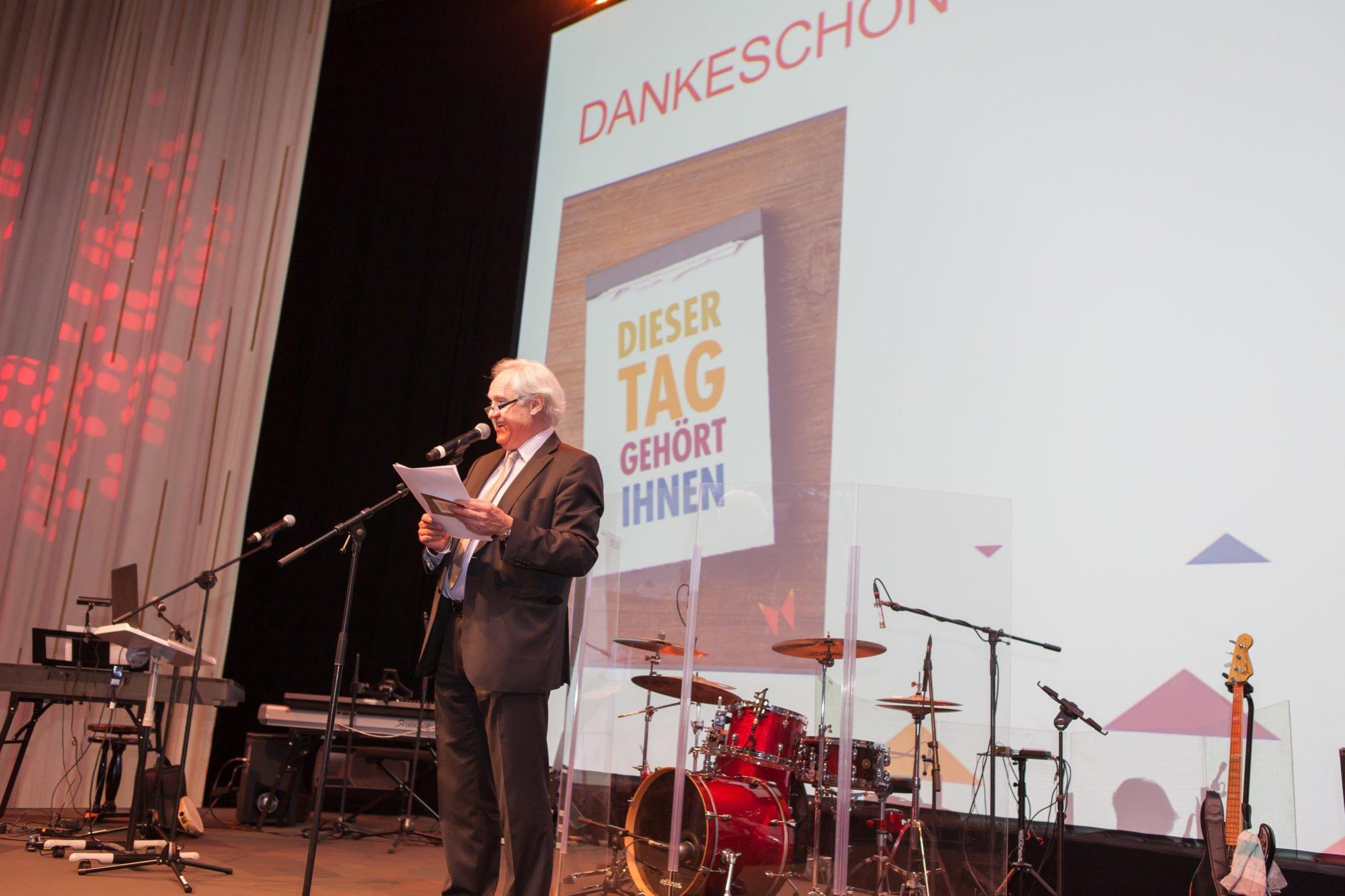 Wolfgang Schrödter auf der Bühne beim Mitarbeiterfest zum 100-jährigen Jubiläum der Stiftung.