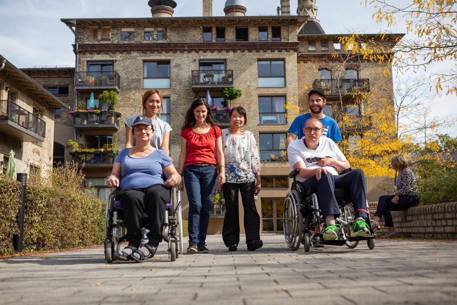 Eine Gruppe Menschen, eine Rollstuhlfahrerin und ein Rollstuhlfahrer, sowie drei Frauen und ein Mann zu Fuß, vor einem alten Backsteingebäude mit Balkons auf denen Pflanzen und Möbel stehen.