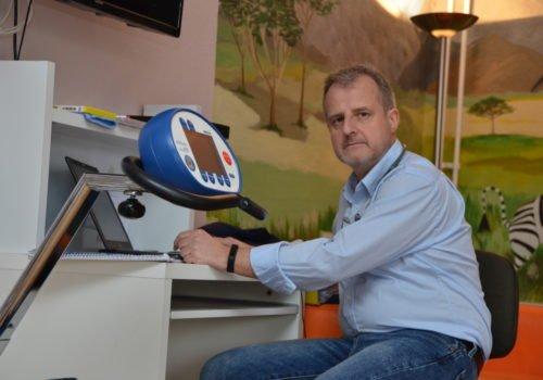 Michael Ertel sitzt am Schreibtisch, vor ihm ein Laptop und Notizblock, er hat ein Stethoskop um den Hals, im Vordergrund erkennt man ein Ergometer, im Hintergrund sieht man eine bemalte Wand mit einer Savannenszene und einem Zebra.