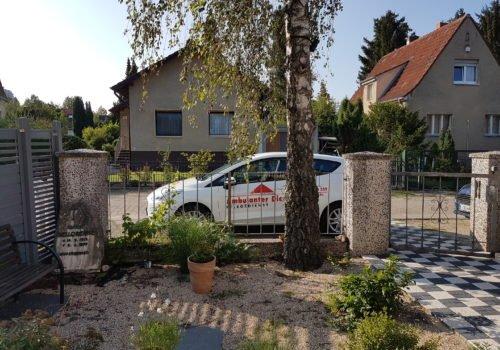 Ein Auto des Ambulanten Dienstes, mit Logos beklebt, steht in einem Wohngebiet am Straßenrand. Das Bild ist aus einem Vorgarten heraus fotografiert. Das Auto steht hinter einem Zaun, davor ein Baum und mehrere Töpfe mit Pflanzen.
