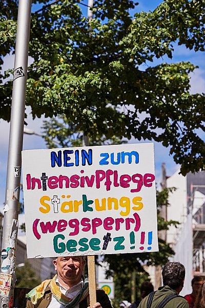 """Ein Mann hält ein Schild mit der Aufschrift """"Nein zum IntensivPflegeStärkungs(Wegsperr)Gesetz!!!"""""""
