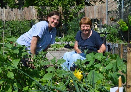 Zwei Frauen stehen bzw. sitzen vor einem Hochbeet und lächeln in die Kamera