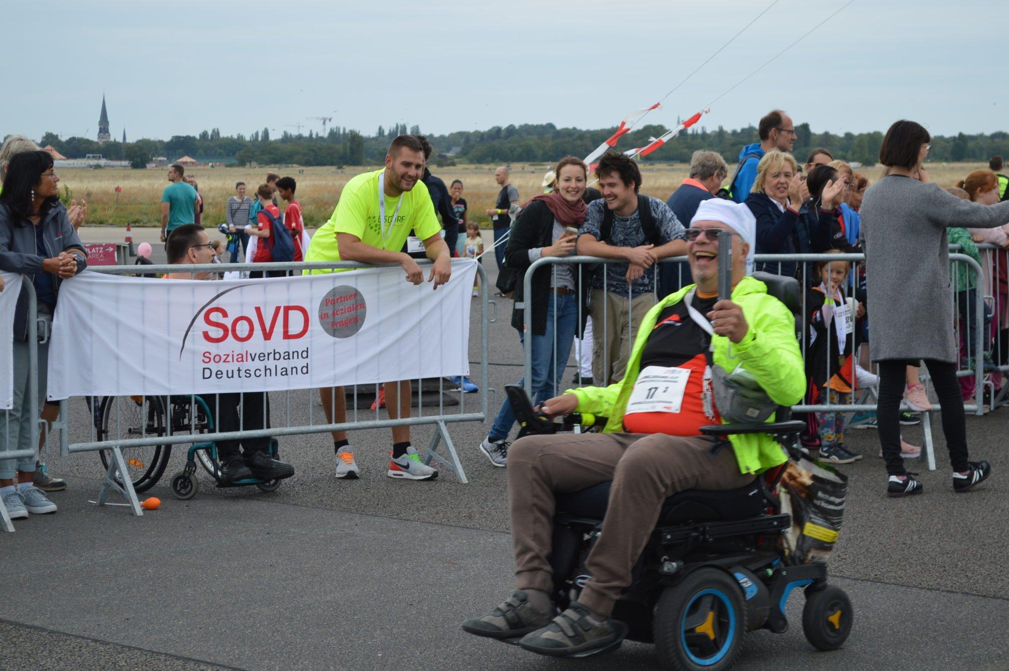 Rollifahrer aus dem Team FDST rollt mit seinem E-Rollstuhl an Zuschauern vorbei und steckt alle mit seinem Lächeln an.