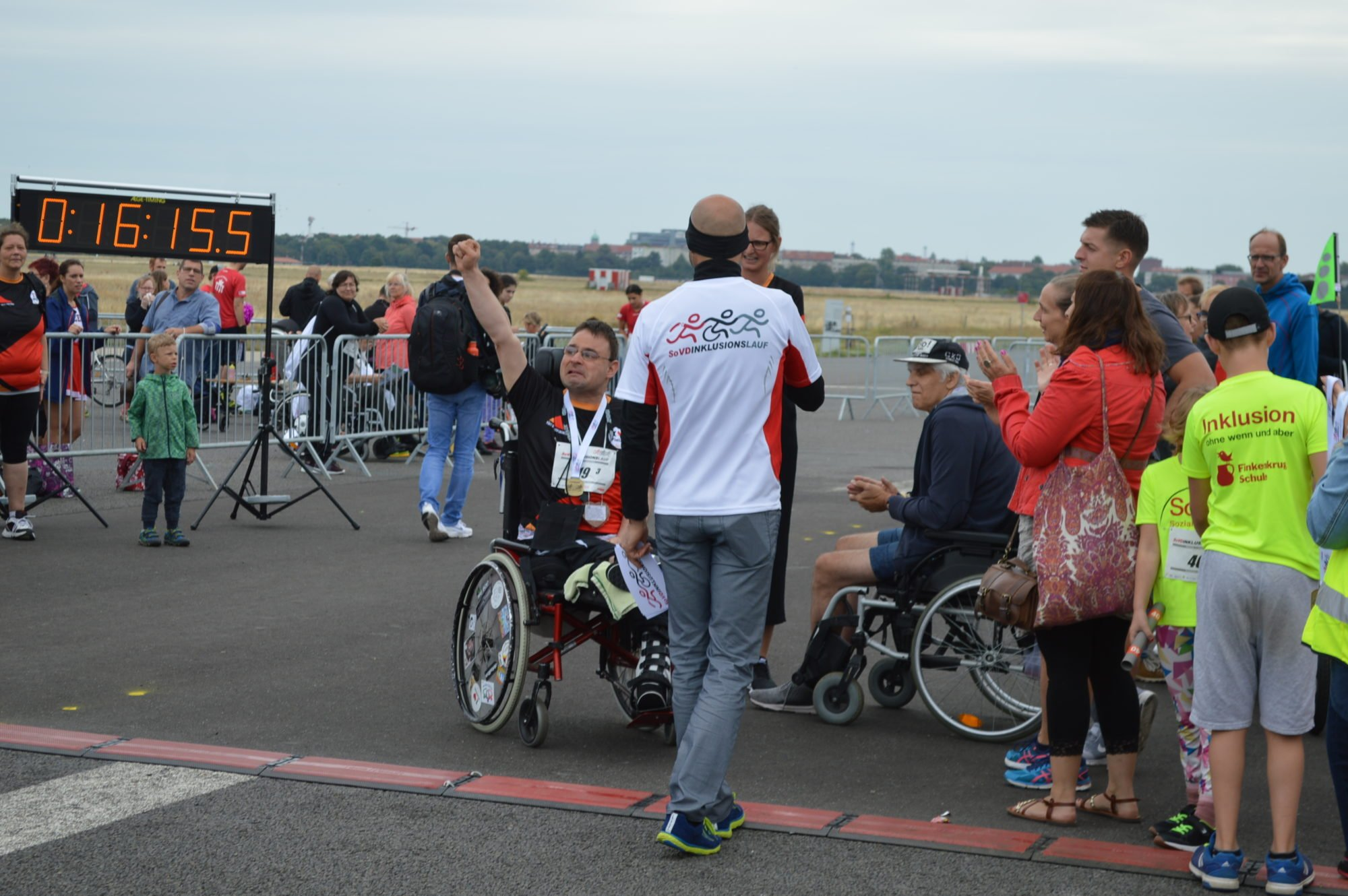 Ein Rollstuhlfahrer aus dem Team FDST reißt die Hand zum Jubel nach oben.