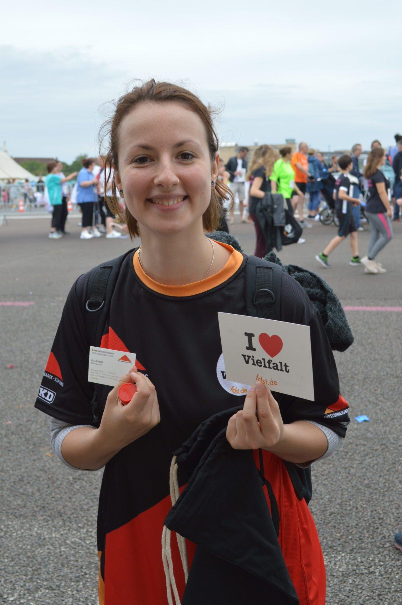 Eine junge Frau hält eine I love VIelfalt Karte nach oben, trägt eines unserer Team-Shirts und lächelt.