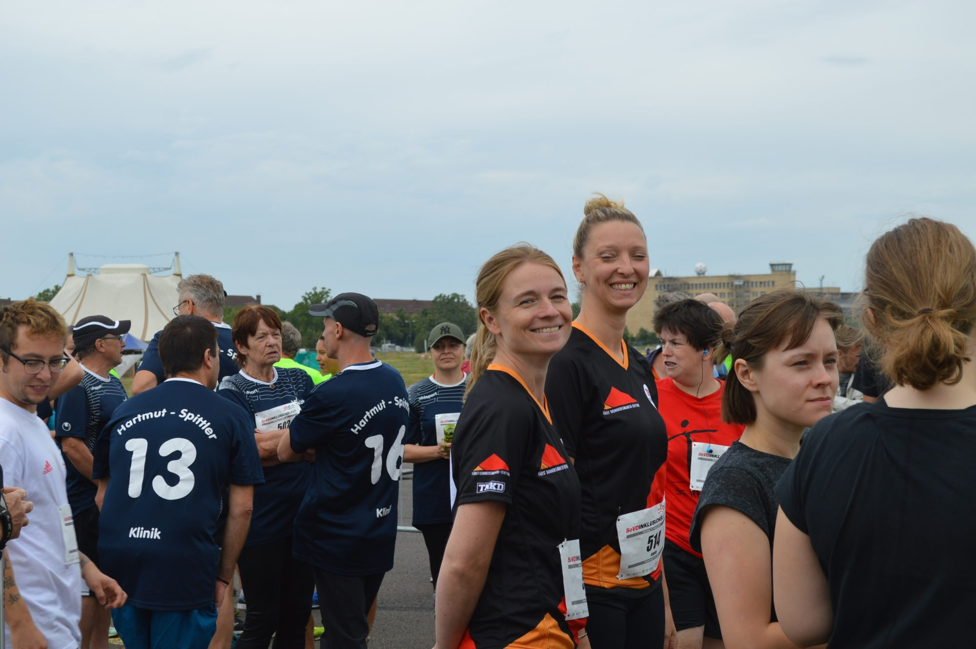 Zwei Teilnehmerinnen aus dem Team stehen in der Menge, drehen sich zur Kamera und lächeln.