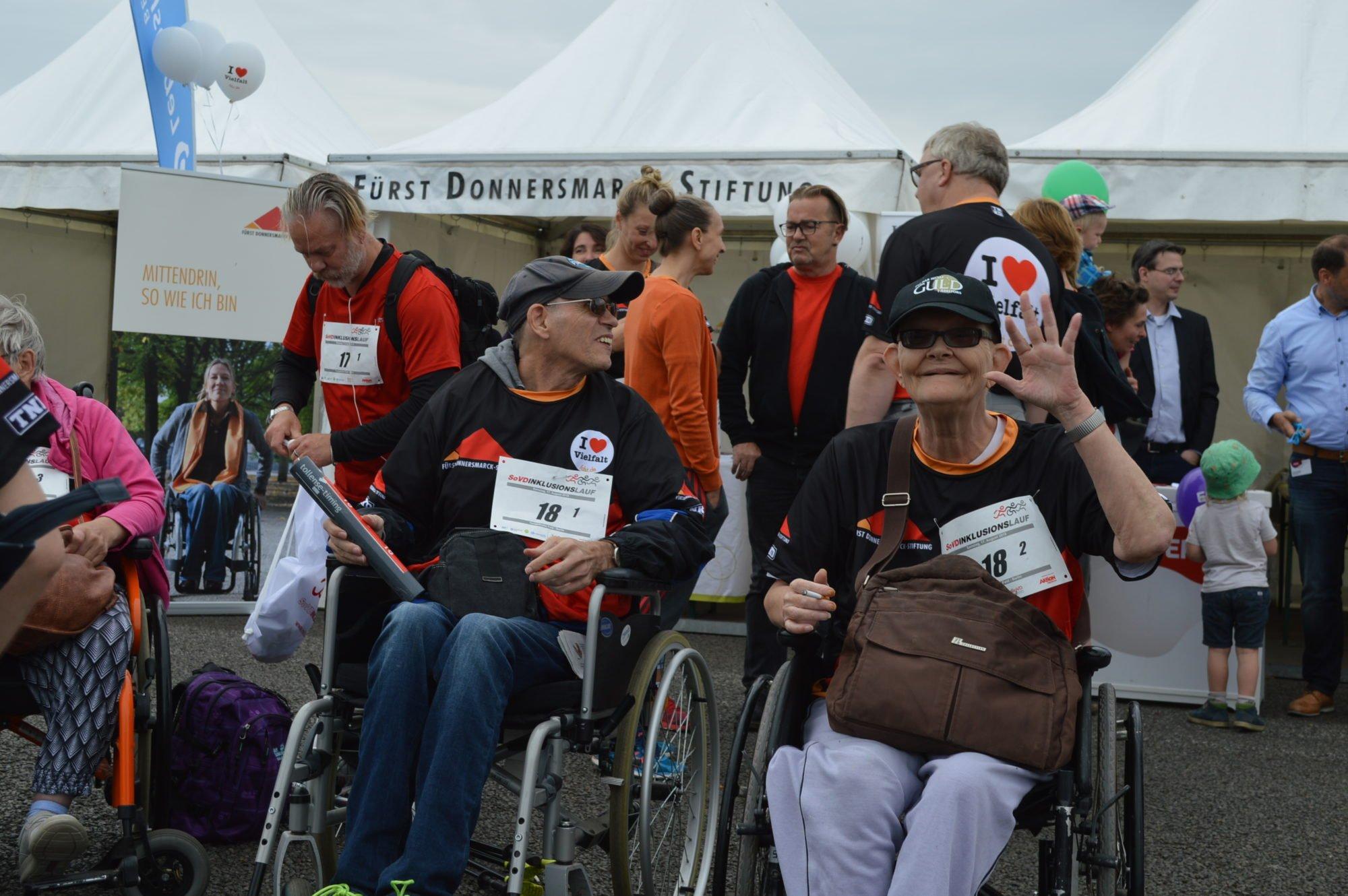 Rollstuhlfahrer und fahrerin vor dem Zelt der FDST, die Rollifahrerin winkt Richtung Kamera.