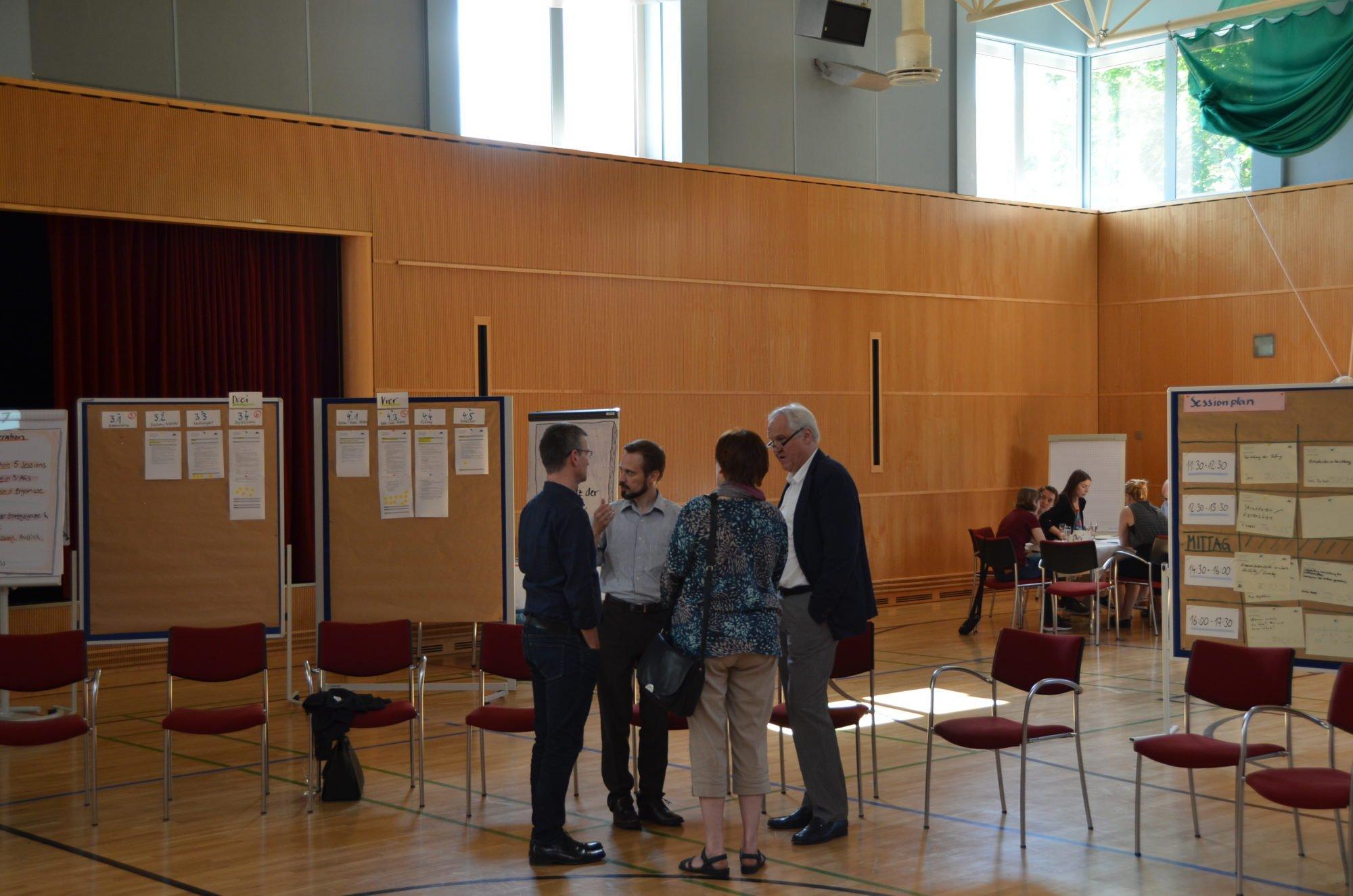 Die Next Generation-Tagung in der Sporthalle des Seehotel Rheinsberg. Wolfgang Schrödter spricht mit dem Führungskreis. Im Hintergrund sieht man Ergebnisse an Whiteboards und Kleingruppen im Austausch.