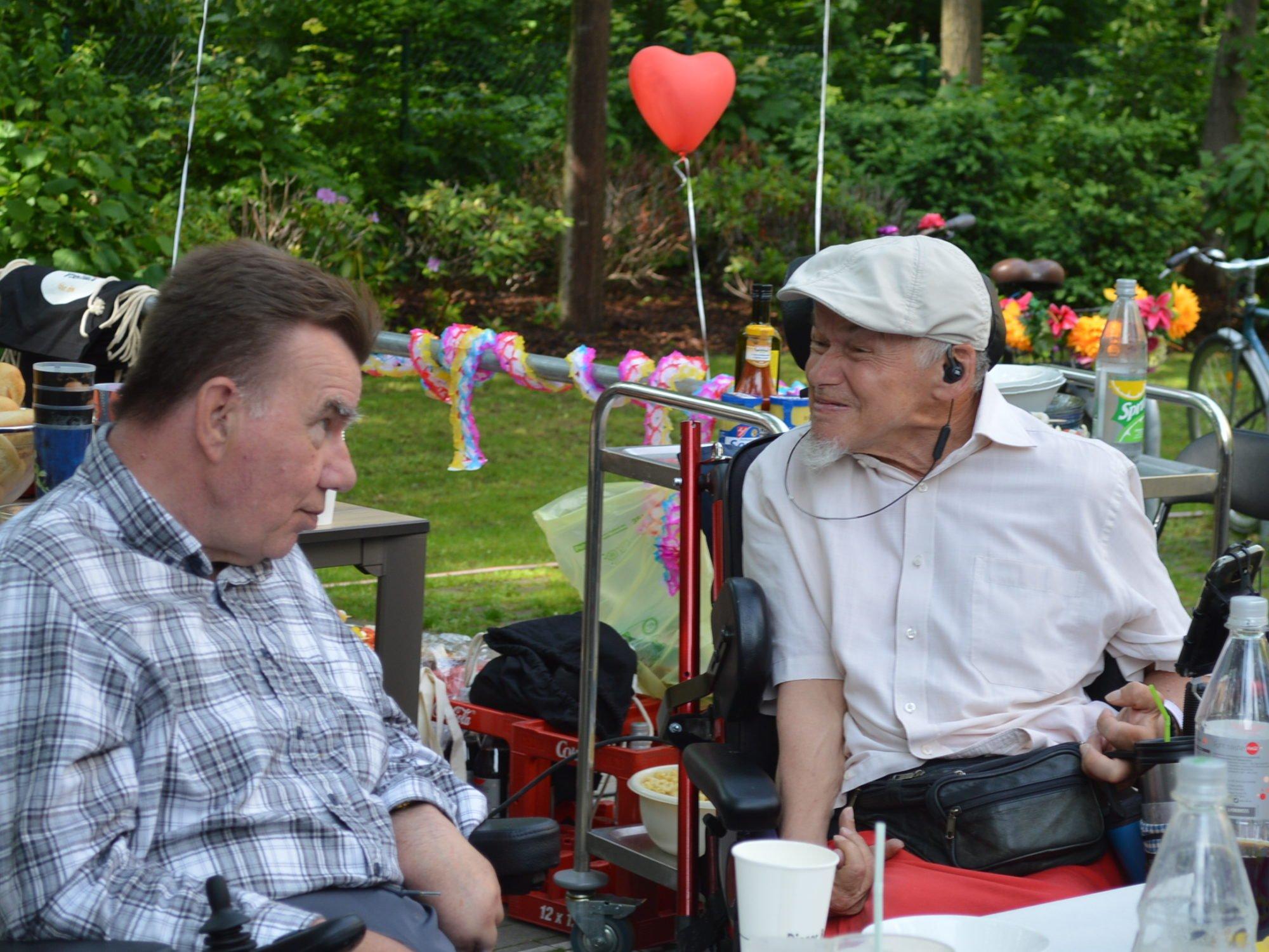 Zwei Herren, beide im Rollstuhl, unterhalten sich. Im Hintergrund der grüne Garten.