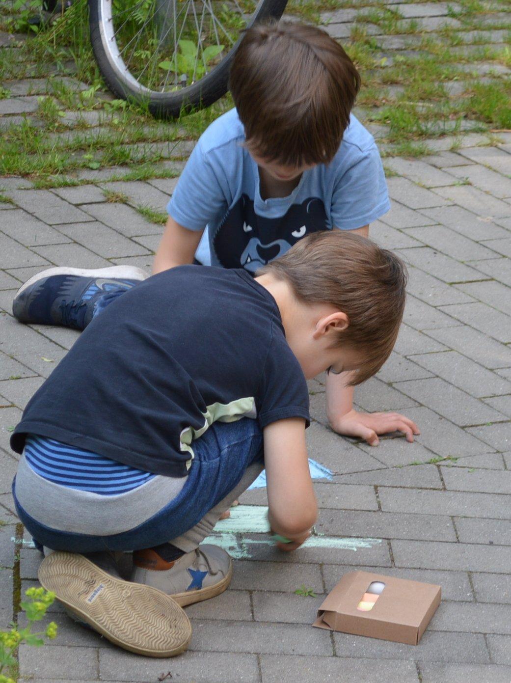 Zwei Kinder malen mit Kreide auf den Steinen vor dem Haus.