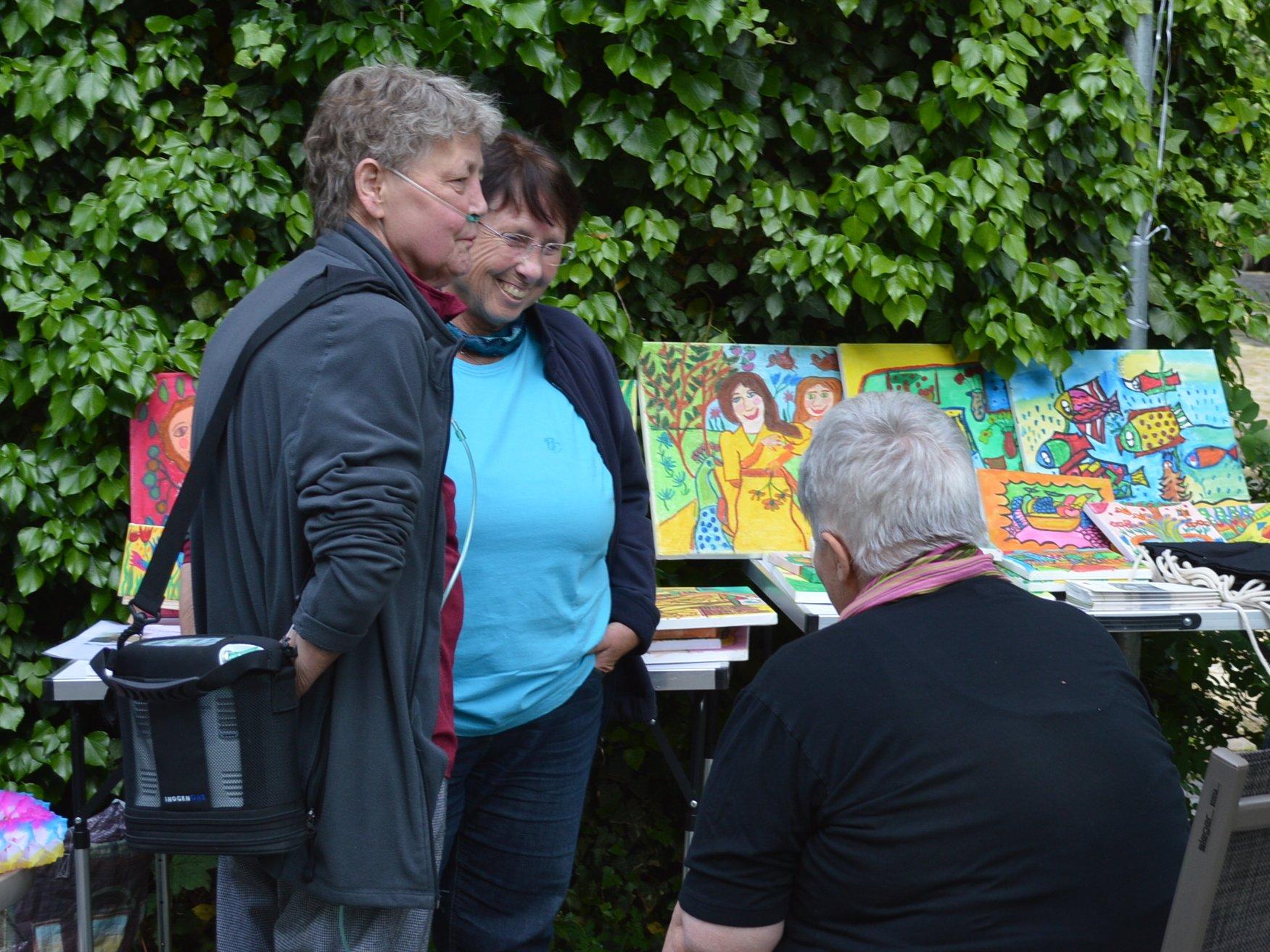 Zwei Damen unterhalten sich mit einer Dame, die ihre selbstgemalten Bilder ausstellt.
