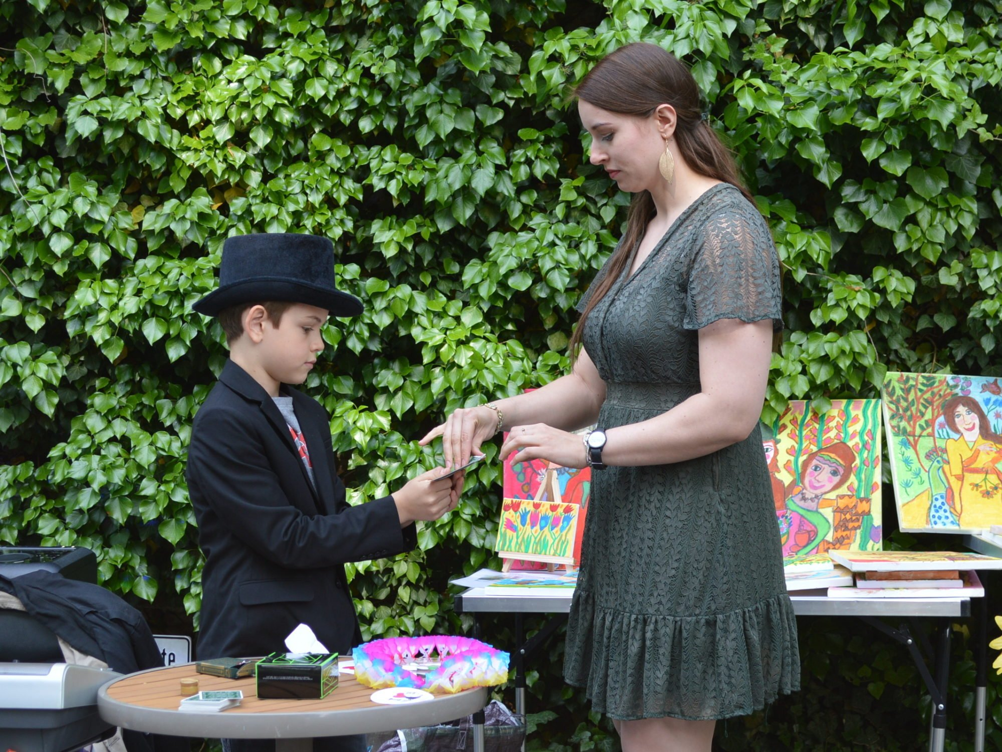 Nachwuchs-Zauberer: Ein kleiner junge mit schwarzem Jacket und Zylinder präsentiert einer Kollegin aus dem WmI einen Kartentrick.