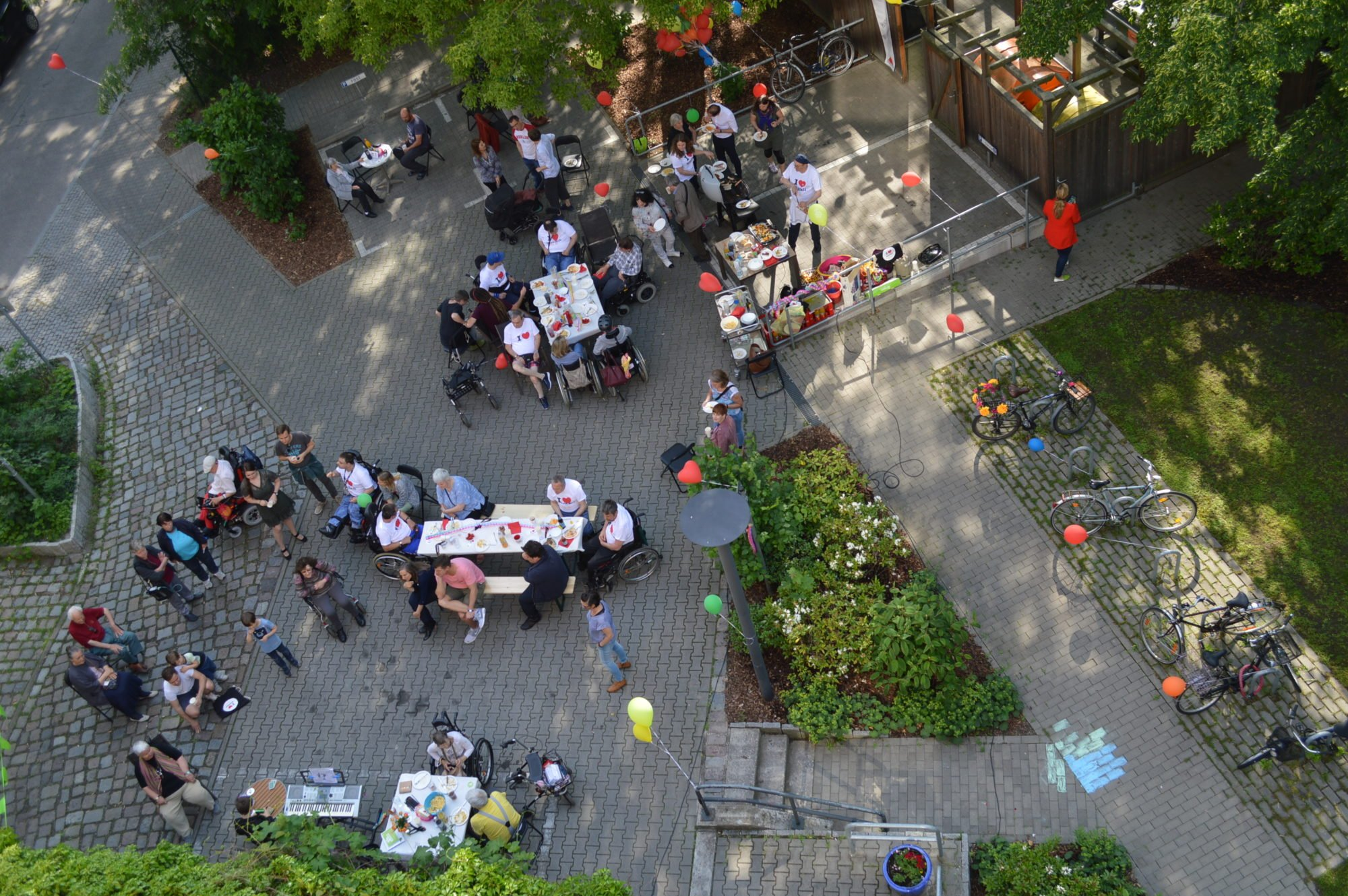 Vogelperspektive: der Tag der Nachbarn 2019 im WmI am Seelbuschring vom Balkon aus fotografiert. Leute stehen und sitzen auf dem Hof, unterhalten sich, essen Gegrilltes und haben eine gute Zeit.