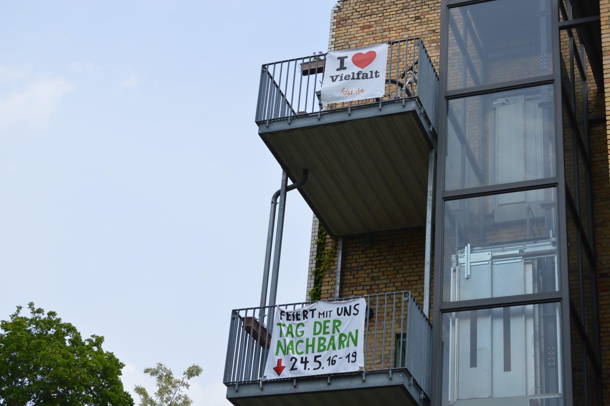 Die Balkons in den oberen Etagen geschmückt mit Bannern: Tag der Nachbarn 2019 und I love Vielfalt.