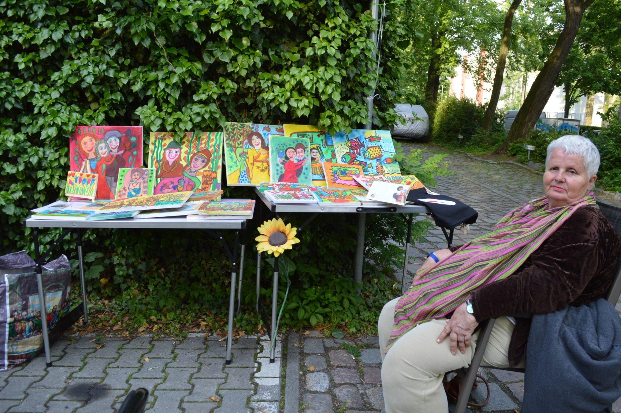 Mini-Kunstaustellung. Eine ältere Dame sitzt bei ihren selbstgemalten Bildern, die sie heute ausstellt.