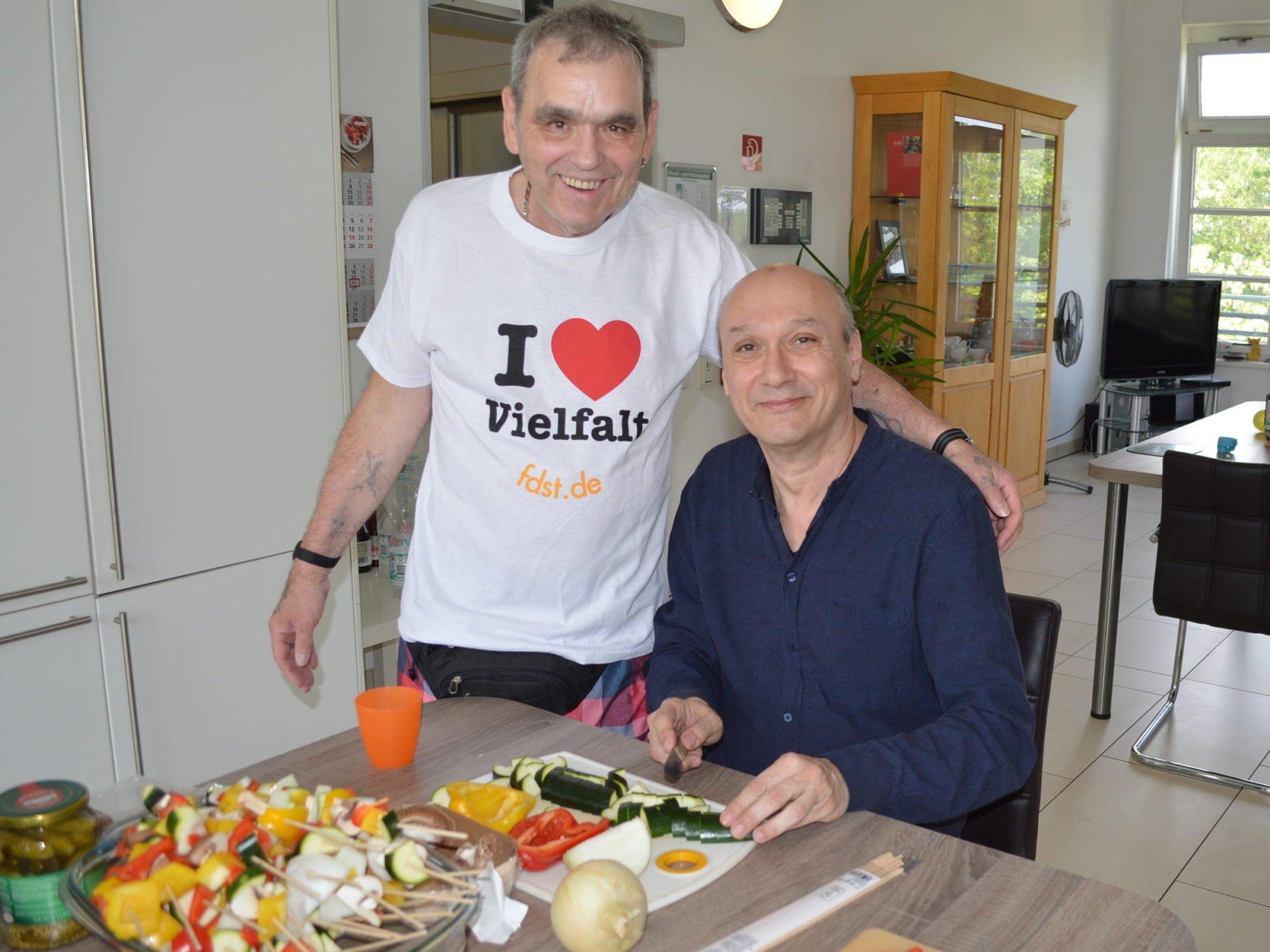 Ein Herr sitzt an einem Tisch und schneidet Gemüse für Grillspieße. Ein anderer Herr steht neben ihm, und trägt ein Shirt mit der Aufschrift I Love Vielfalt. Beide schauen in die Kamera und lächeln.