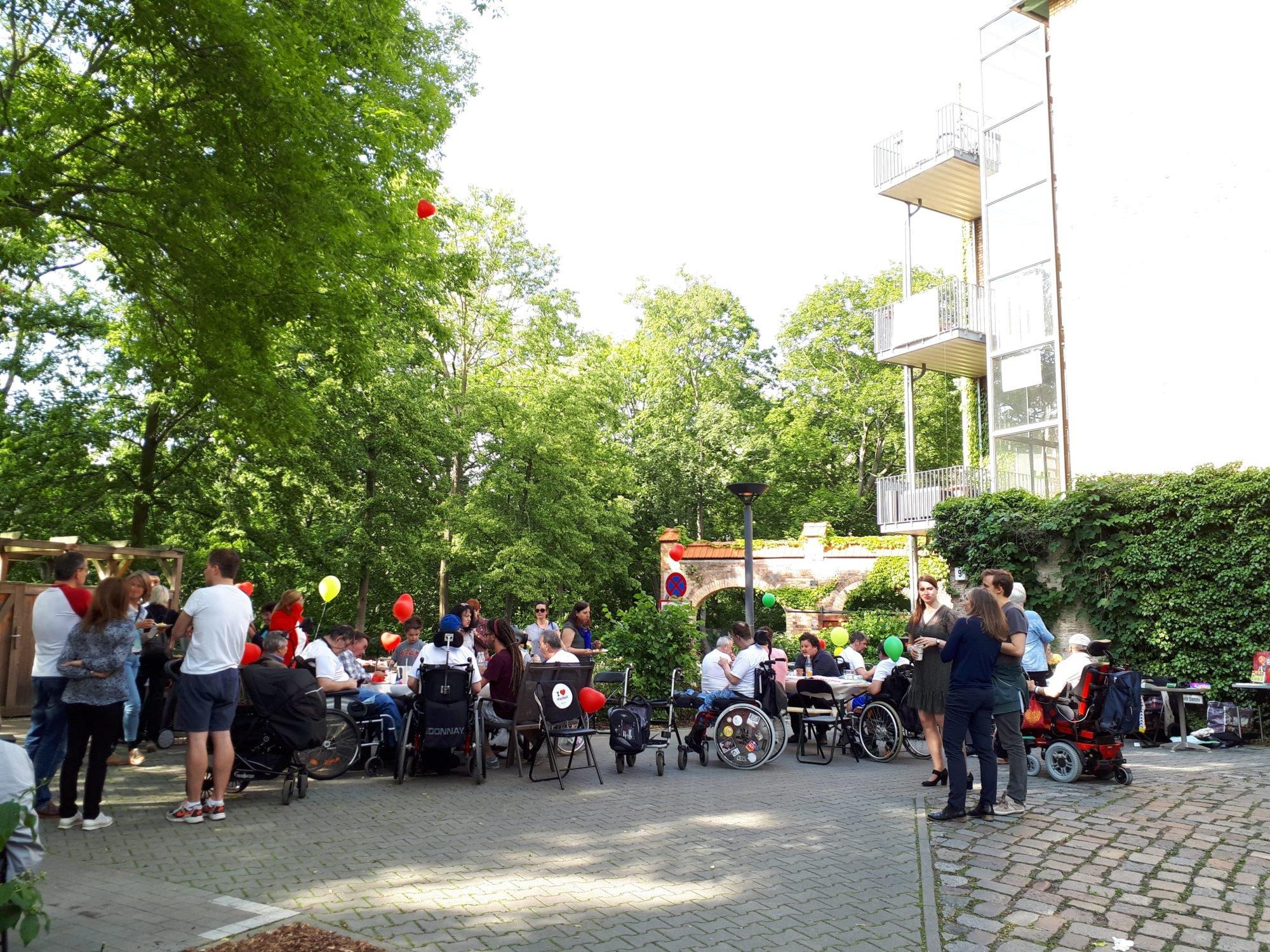 Ein schönes Fest - Blick auf das Gebäude und auf den Hof mit den Tischgruppen. Menschen sitzen und stehen hier, unterhalten sich oder essen und haben eine schöne Zeit.