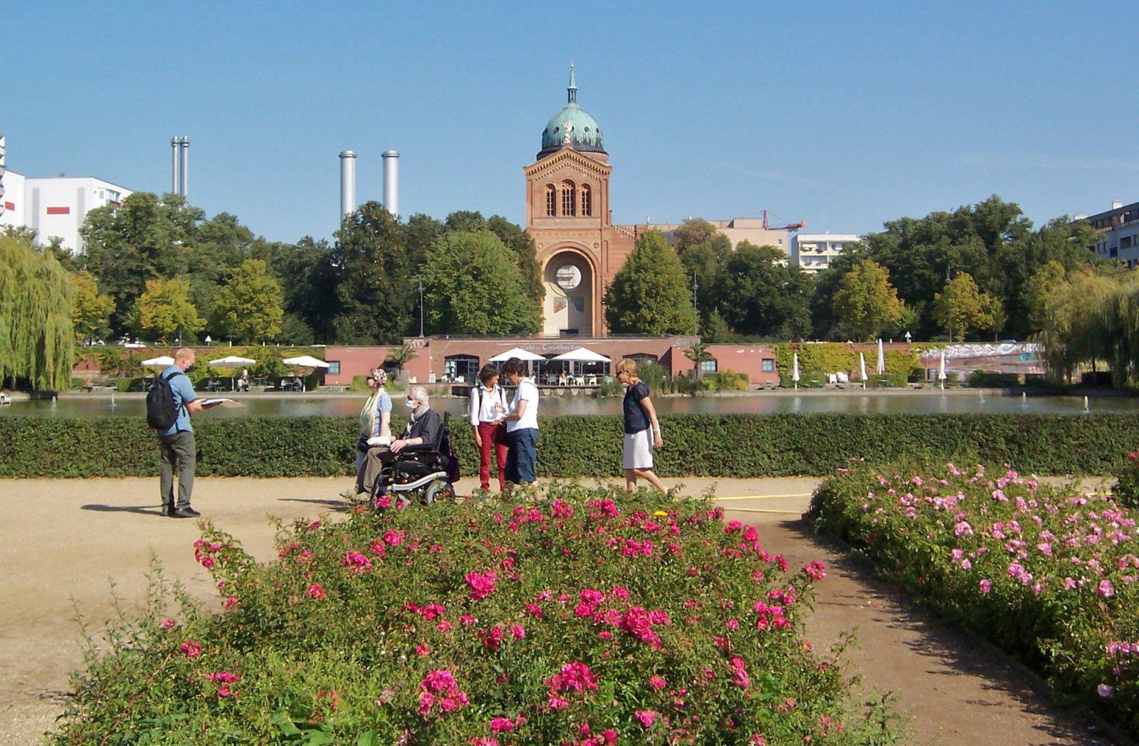 Blumenbeete am Luisenstädtischen Kanal mit einer Spaziergruppe im Rolli