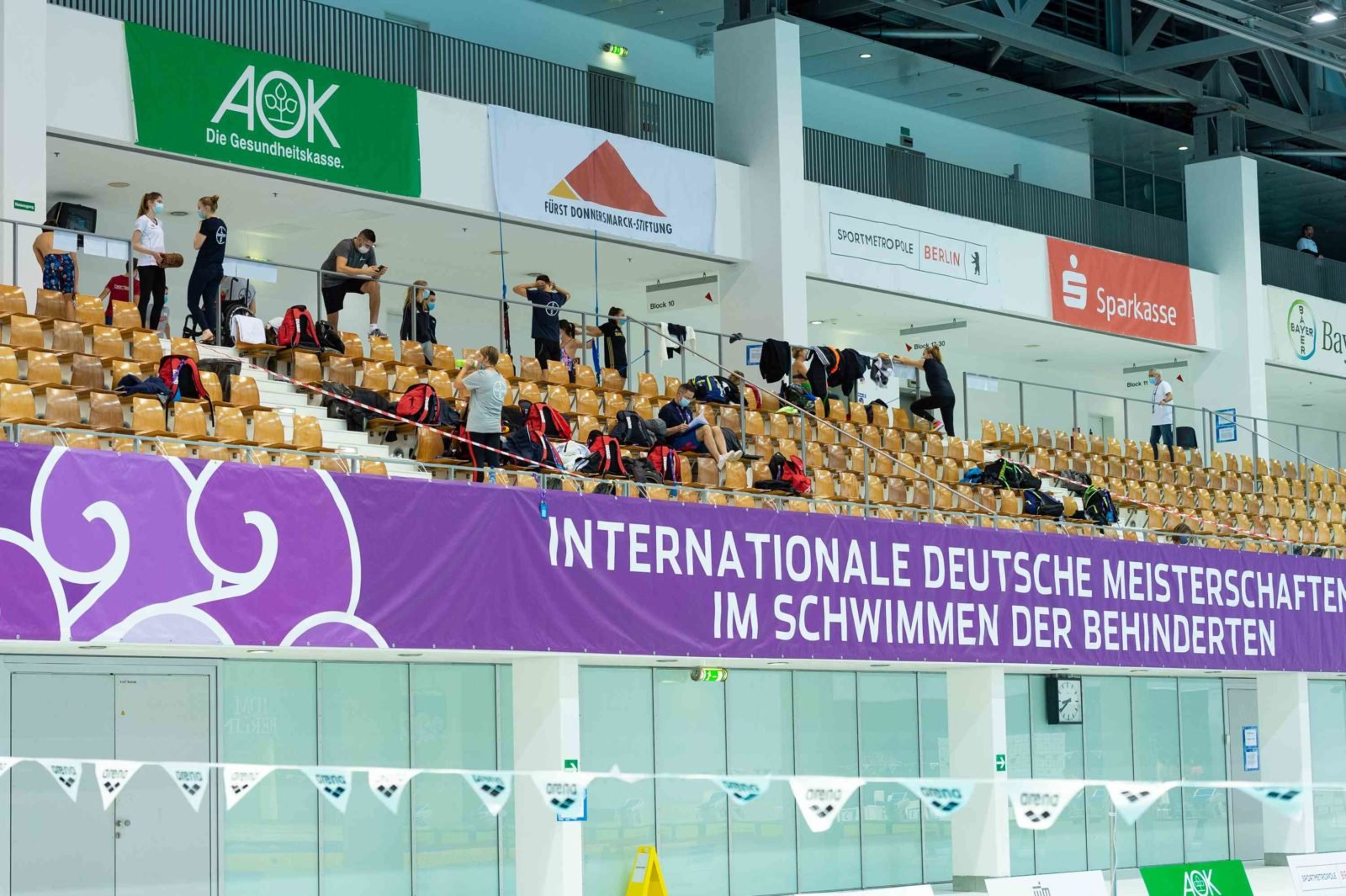 Die Tribüne der IDM 2020. Wenige Personen sind zu sehen, alle tragen Mundschutz. Im oberen Teil des Bildes sieht man das Logoder Fürst Donnersmarck-Stiftung