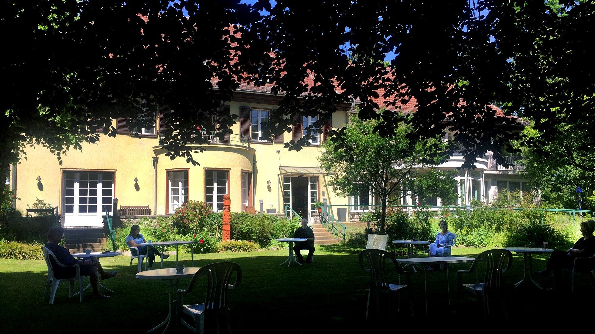 Blick aus dem Garten auf die Villa Donnersmarck, die im Hintergrund zu sehen ist. Davor an mit großem Abstand gestellten Tischen, Mitarbeitende bei ihrer Besprechung
