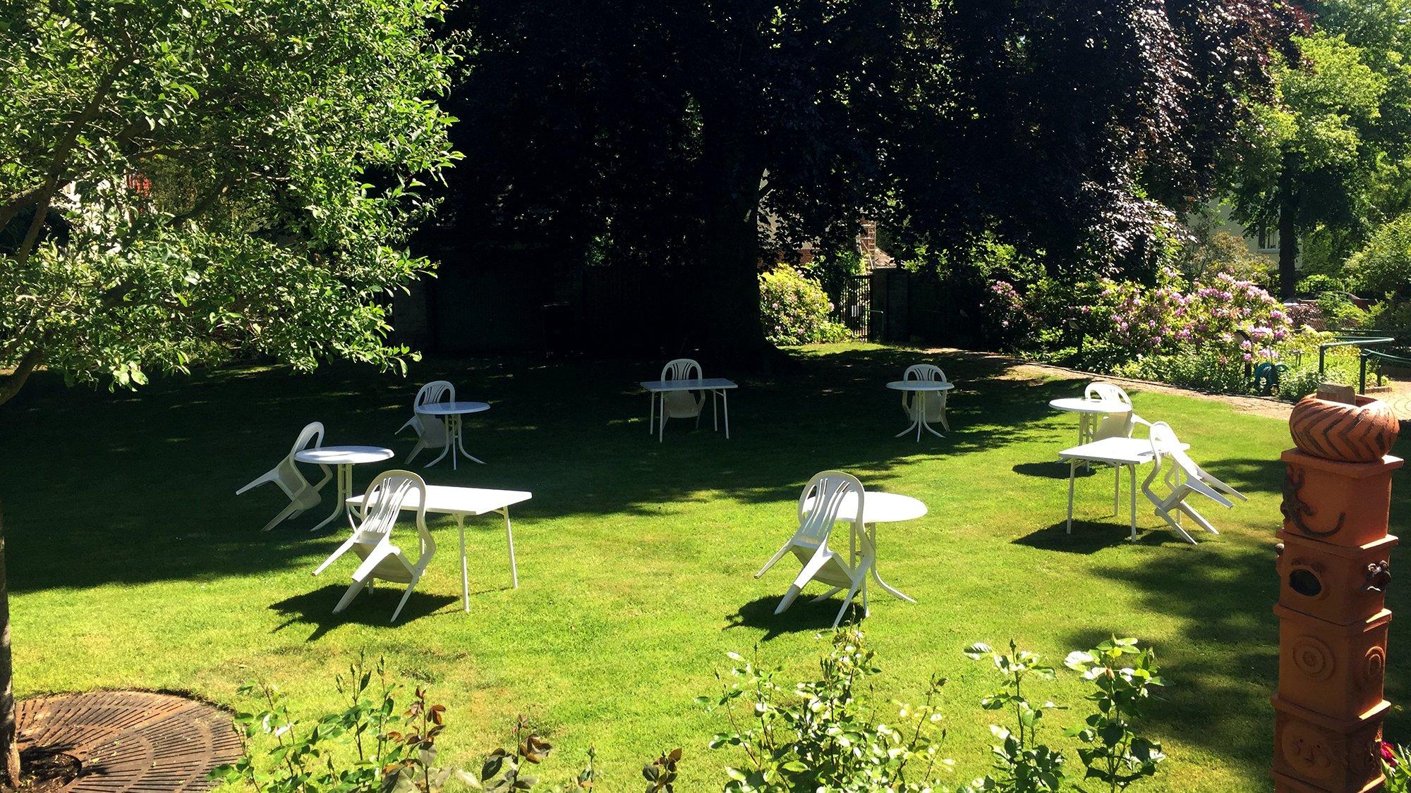 Blick in den Garten der Villa Donnersmarck: acht Tische und Stühle im Kreis mit viel Abstand gestellt auf dem Rasen
