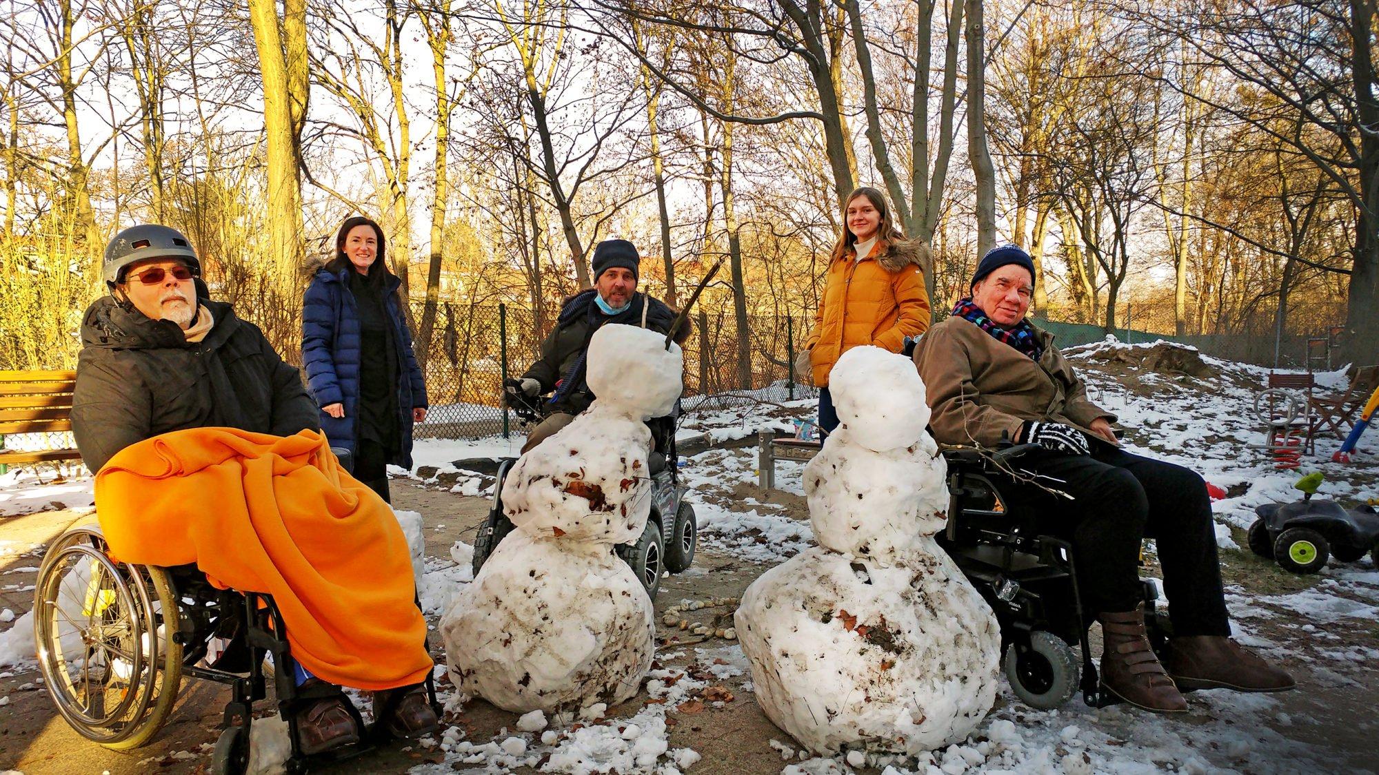 Eine Gruppe aus drei Herren im Rollstuhl und zwei Damen hinter zwei Schneemännern an einem sonnigen Wintertag
