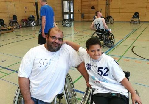 Ayman Mohsen posiert mit seinem Sohn in einer Sporthalle. Sein Sohn legt den Arm um seinen Vater - beide sitzen in einem Rollstuhl.