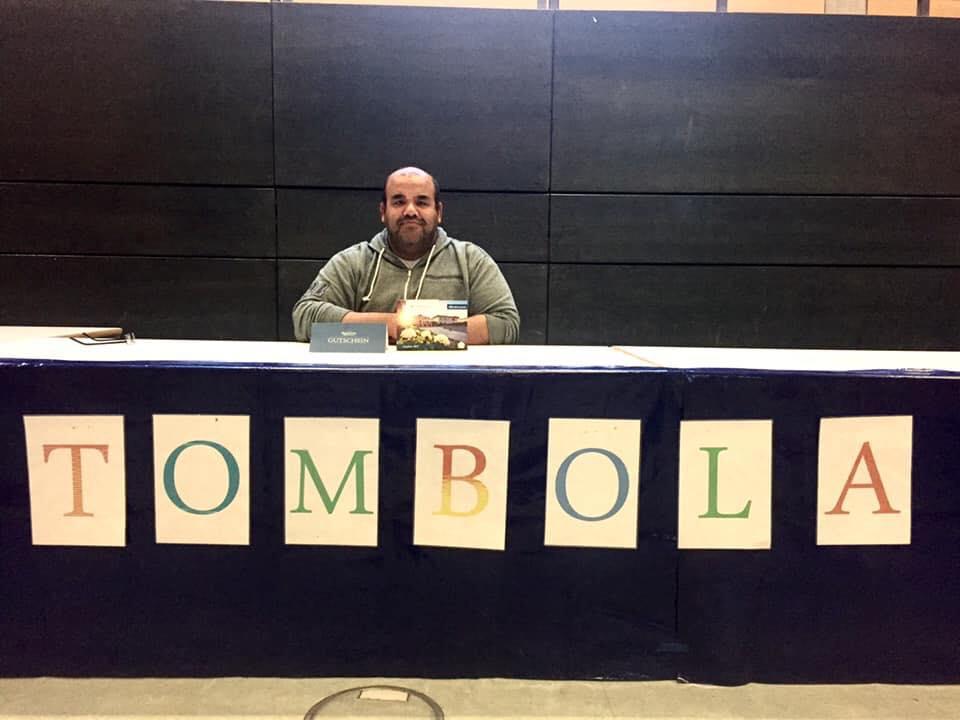 Ayman Mohsen sitzt an einem langen Tisch auf dem in Großbuchstaben Tombola steht.
