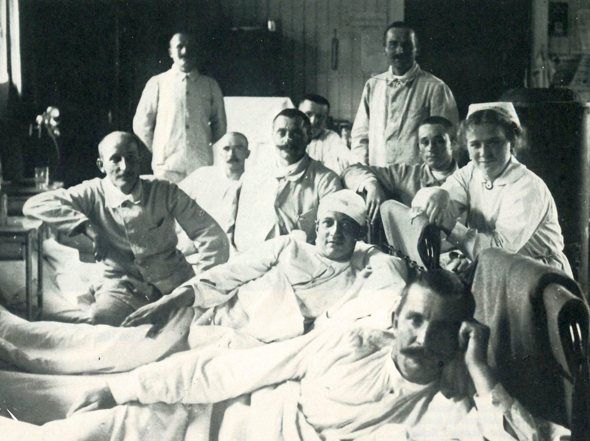 Ein historiches Schwarz-Weiß Foto: Mehrere Männer in und um ihre Betten im Vereinslazarett. Rechts im Bild auch eine Krankenschwester.