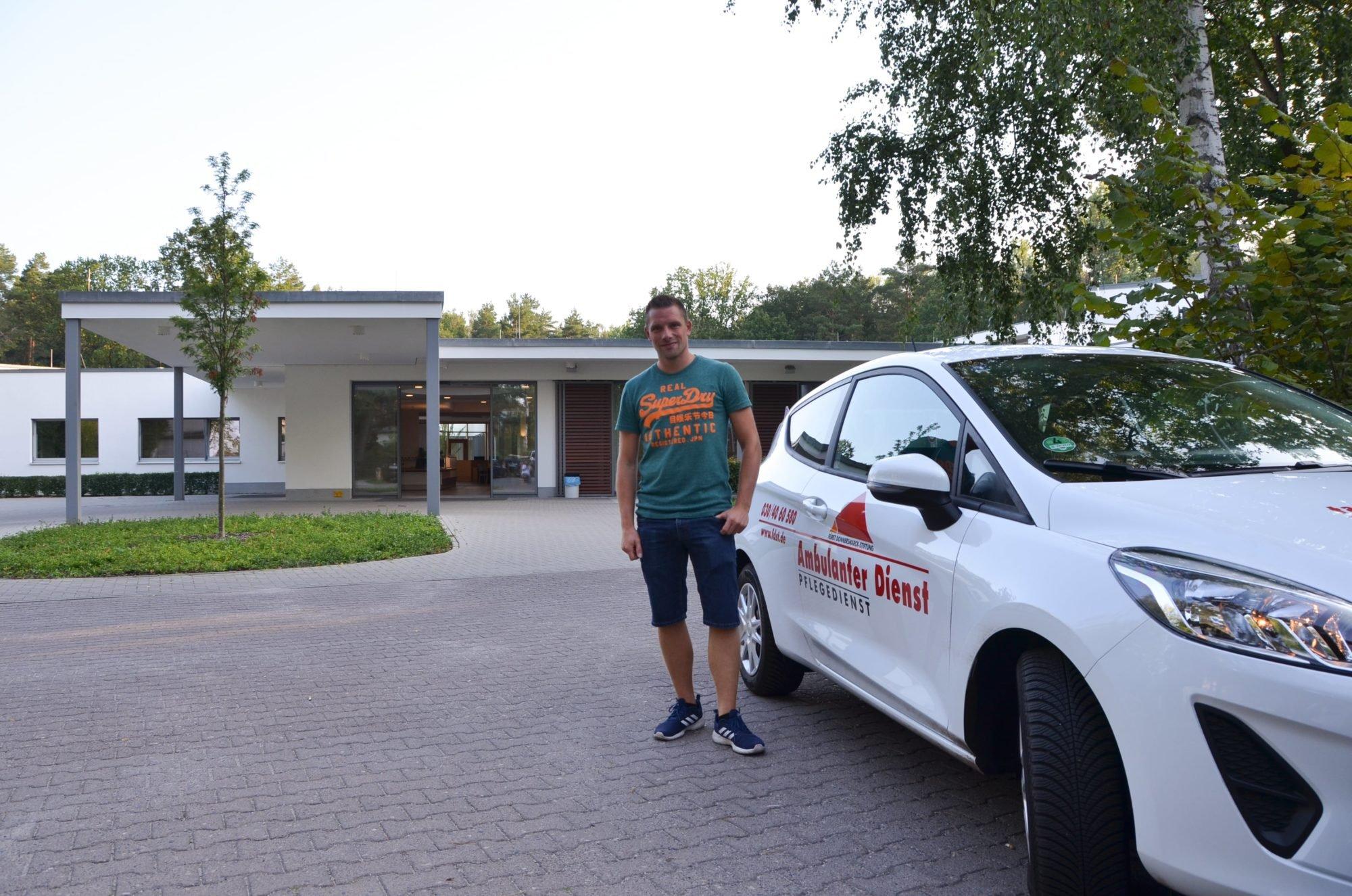 Pflegefachkraft Marco Noack steht neben dem Auto des AD vor dem P.A.N. Zentrum