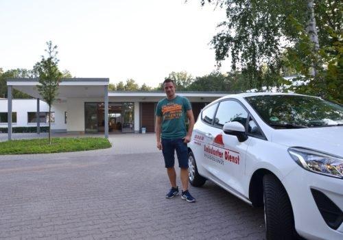 Pflegefachkraft Marco Noack mit einem AD-Auto vor dem P.A.N. Zentrum