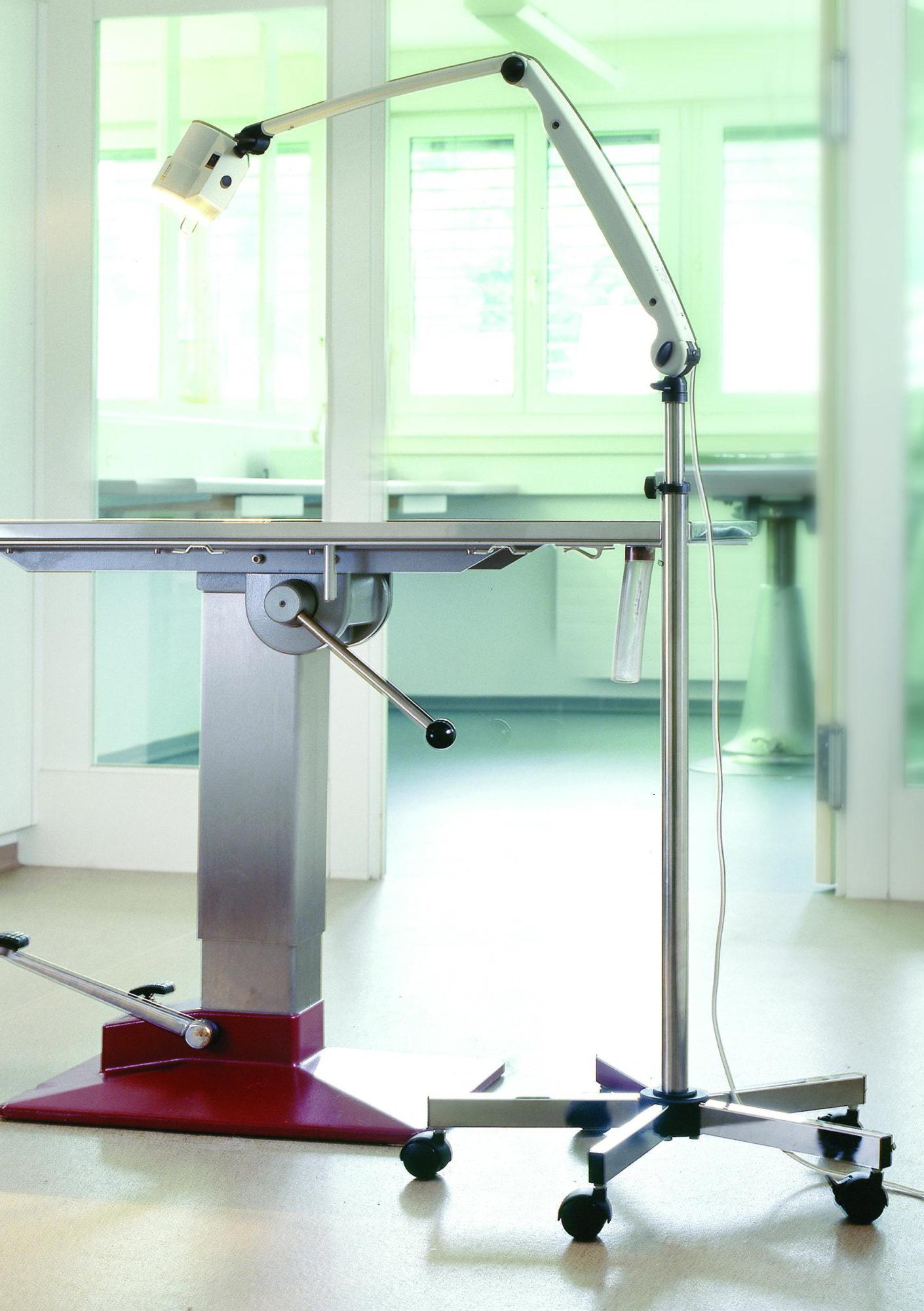 Ein Behandlungsraum mit höhenverstellbarer, mobiler Untersuchungsliege und einer bewegbaren Leuchte.