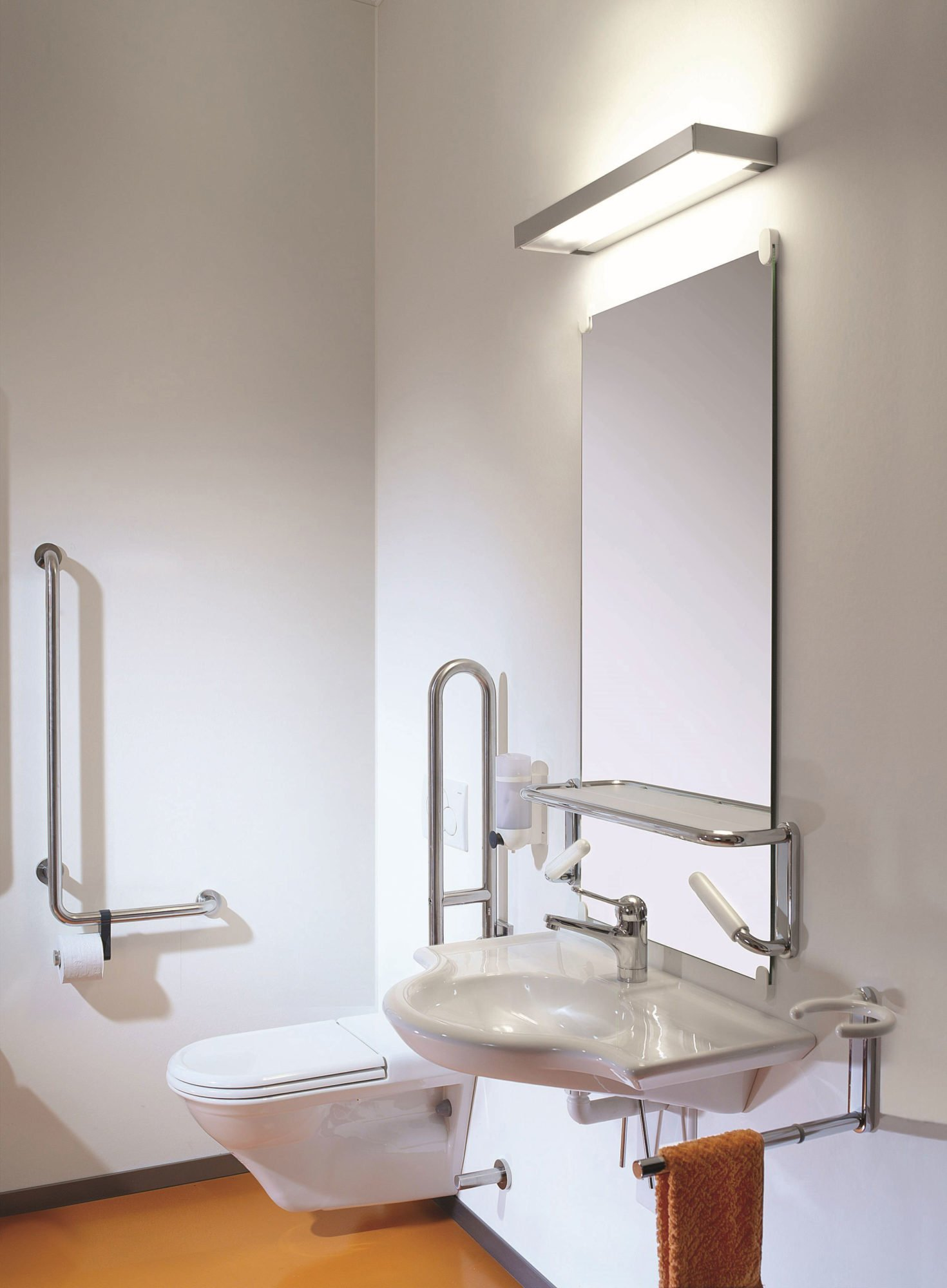 Zu sehen ist ein barrierefreies WC. Ein unterfahrbares Waschbecken und ein Spiegel mit Lampe.