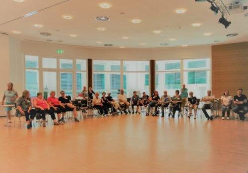 Eine große Gruppe Menschen, teilweise mit Rollstuhl, sitzt in einer großen Halle im Halbkreis. Im Hintergrund große Fenster.